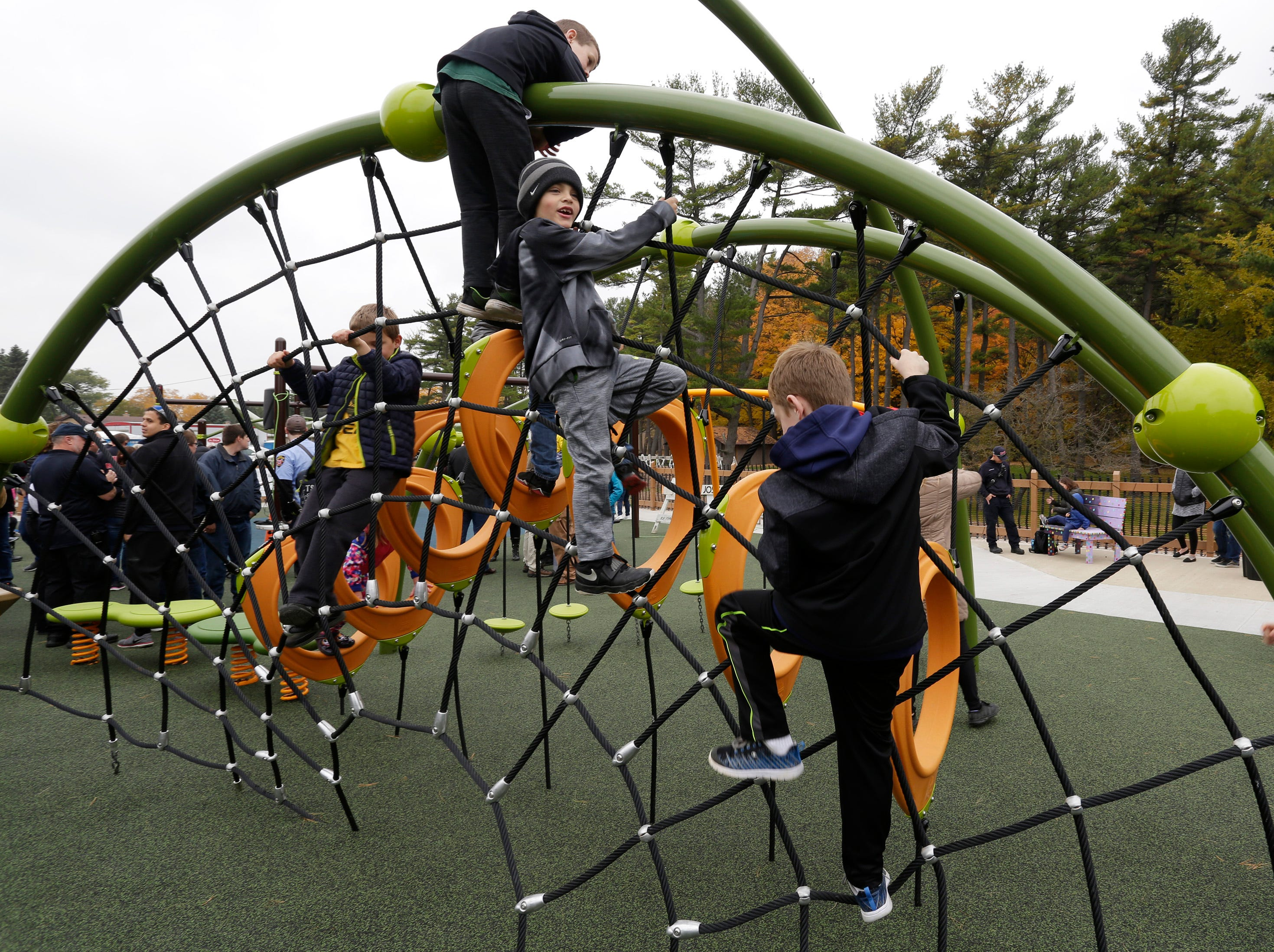 Children crawl about the Shaw Family Playground, Saturday, September 27, 2018, in Sheboygan, Wis. The playground held a ribbon cutting event to showcase the adaptive playground that is accessible for children of all physical abilities.