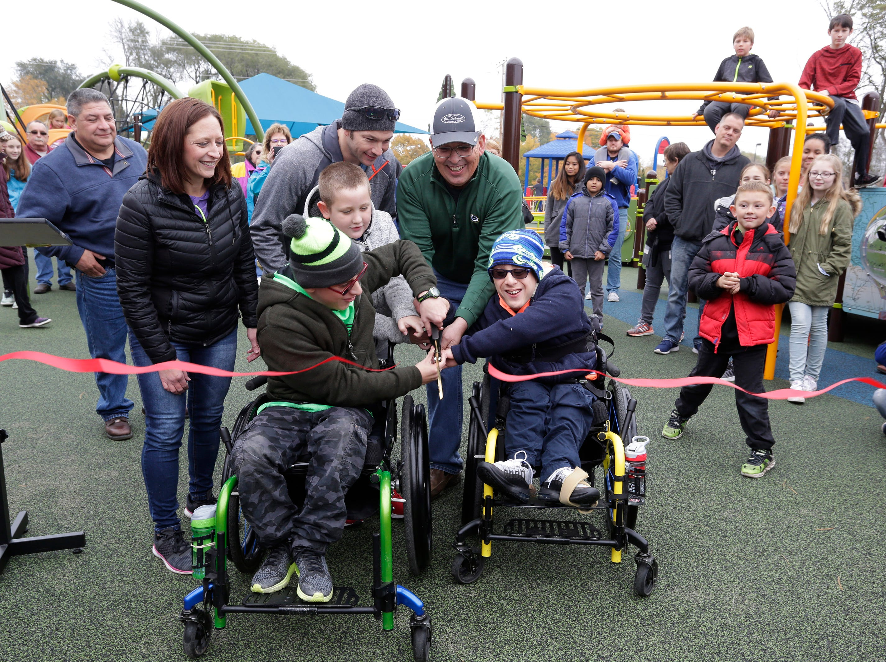 Mateo Shaw, left, and his brother McHale, both 12, cut the ribbon for the Shaw Family Playground, Saturday, September 27, 2018, in Sheboygan, Wis. The adaptive playground is an area that is accessible for children of all physical abilities.
