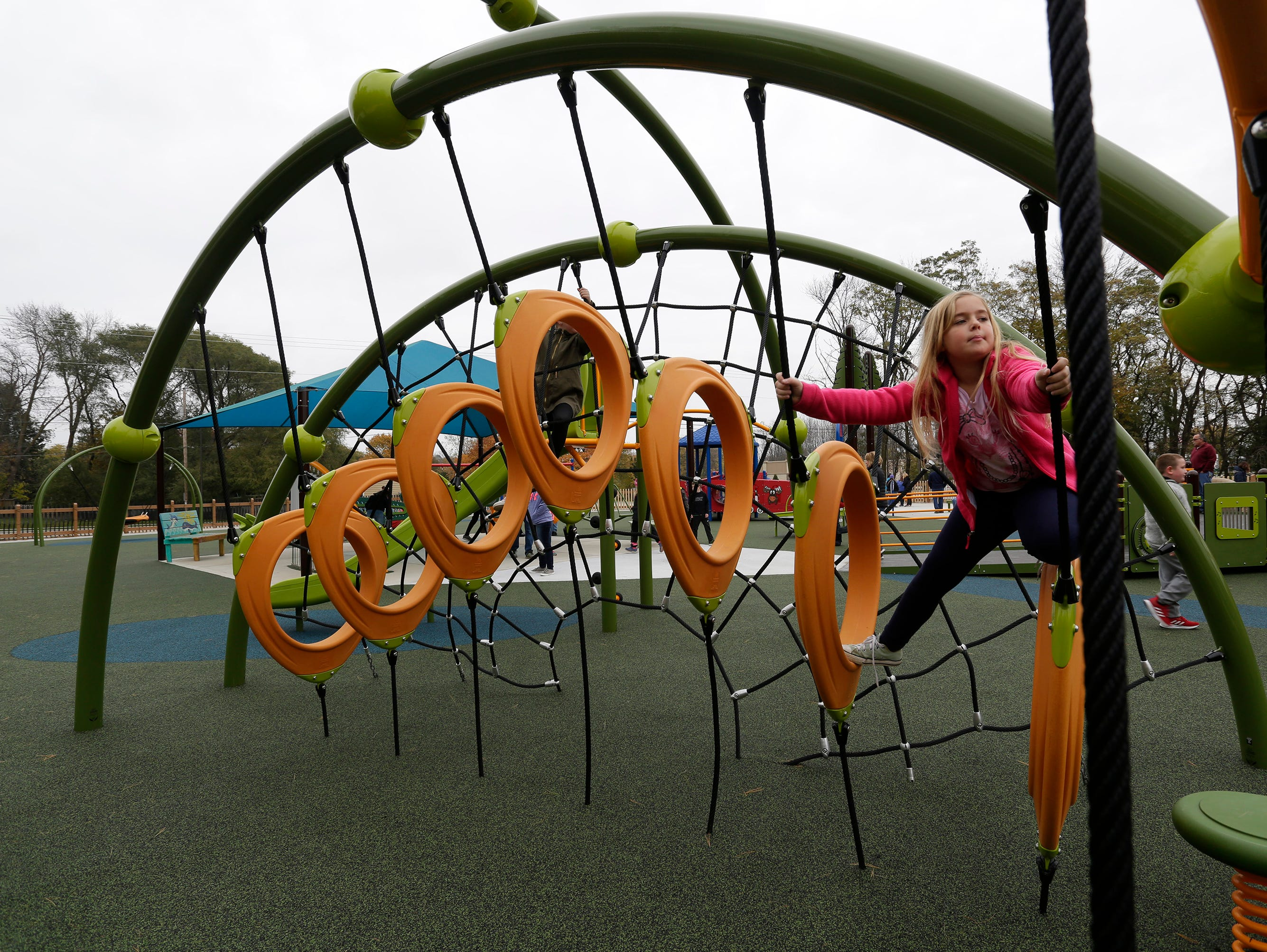 A young girl tests her skills at the Shaw Family Playground, Saturday, September 27, 2018, in Sheboygan, Wis. The playground held a ribbon cutting event to showcase the adaptive playground that is accessible for children of all physical abilities.