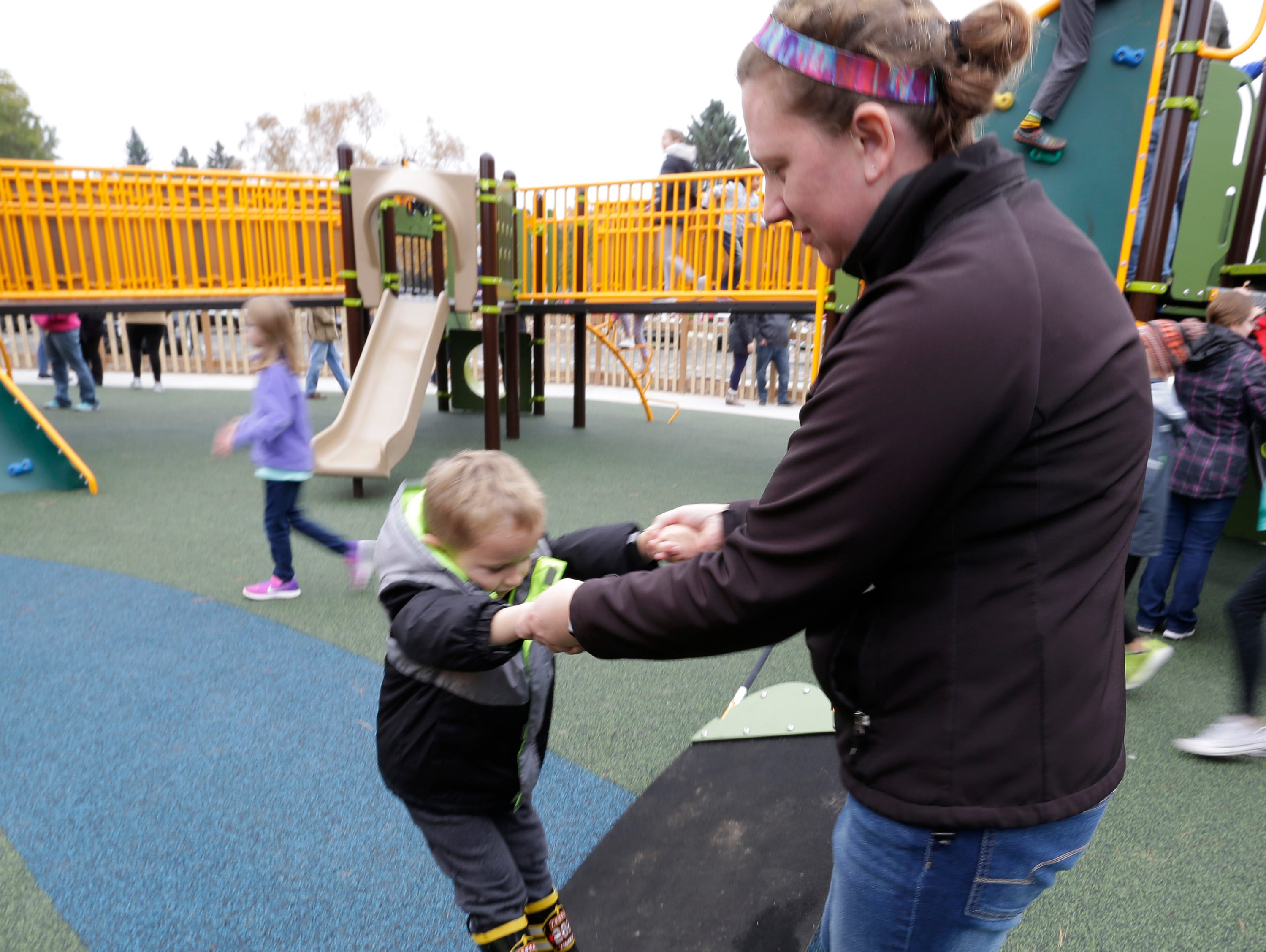 Avery Ponath, 4, is helped by his mom Jennifer on a piece of playground gear at the Shaw Family Playground, Saturday, September 27, 2018, in Sheboygan, Wis. The playground held a ribbon cutting event to showcase the adaptive playground that is accessible for children of all physical abilities.