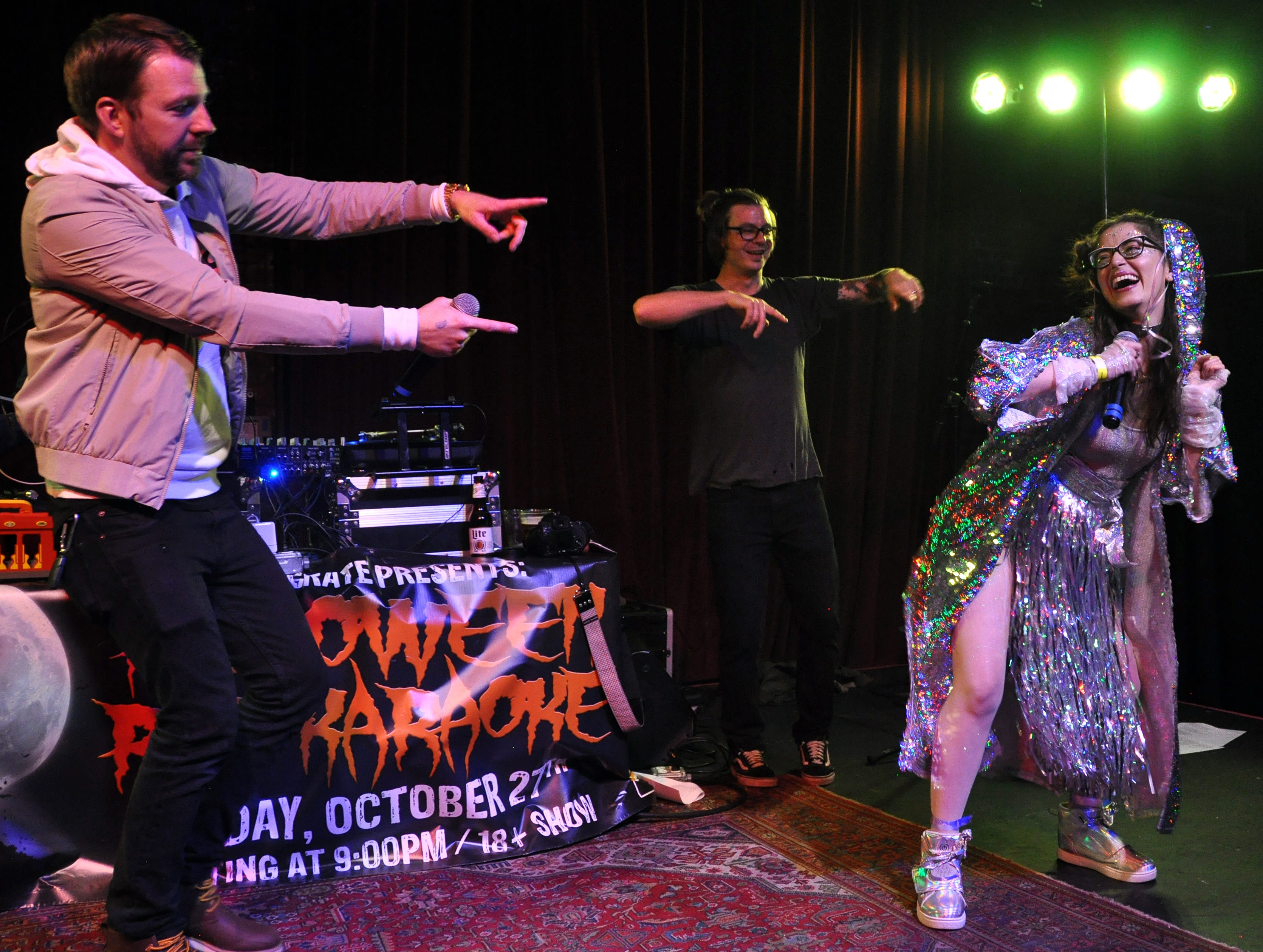 Catherine Holland gets some encouragement from Danny, left, and Wes Eisenhauer during her performance at the 10th Annual Halloween Rap Karaoke show at Icon Lounge Friday night. The event is was created by the Sioux Falls band Soulcrate.