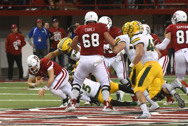 University of South Dakota's Austin Simmons (3) is taken down as he carries the ball against North Dakota State in Vermillion on Saturday, Oct. 27, 2018.
