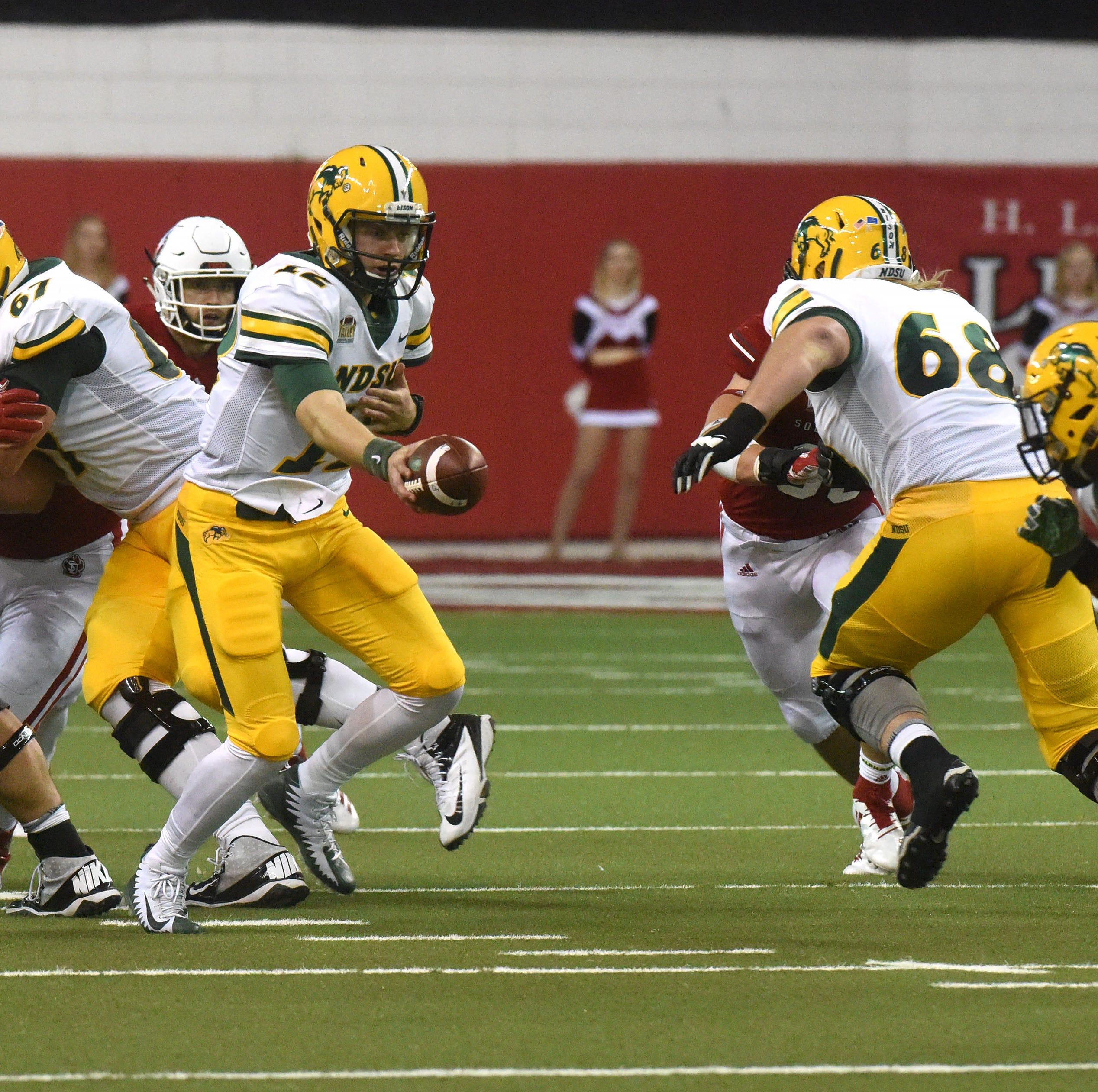 North Dakota State's Easton Stick (12) goes to hand the ball off during a game against University of South Dakota in Vermillion, S.D., Saturday, Oct. 27, 2018.
