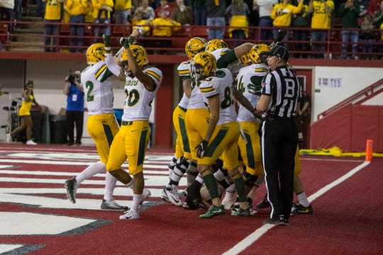 North Dakota State players celebrate their first touchdown during a game against University of South Dakota in Vermillion, S.D., Saturday, Oct. 27, 2018.