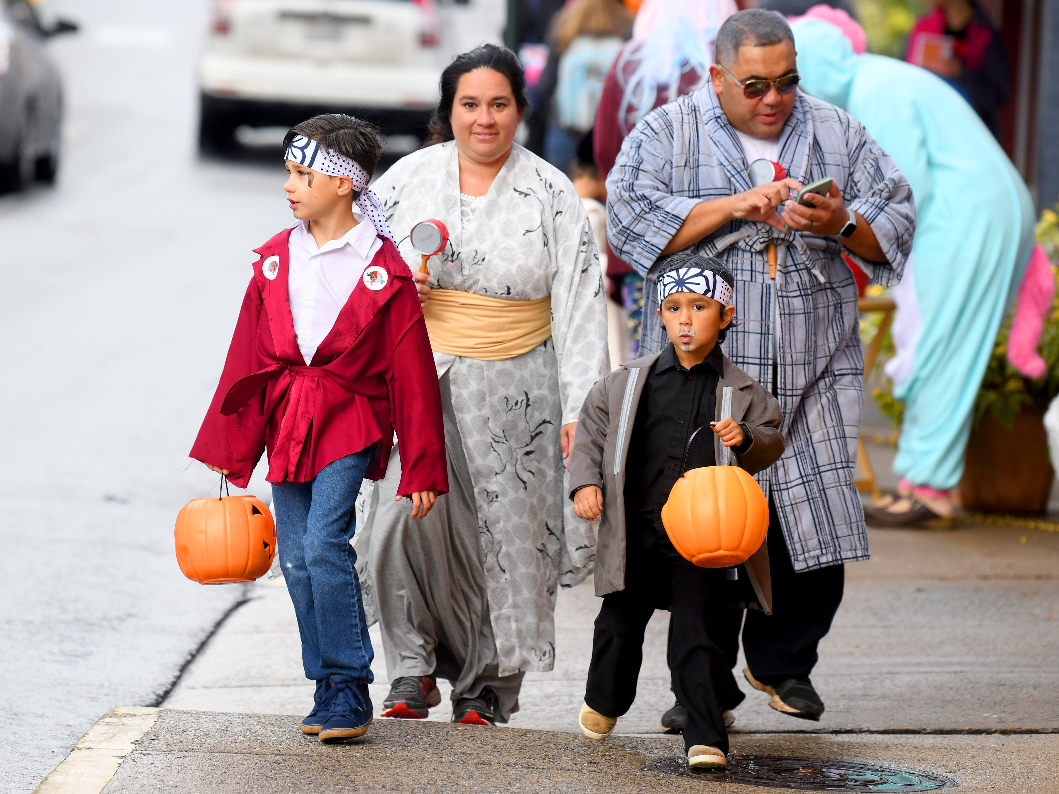 A family shares a common theme as they trick-or-treat together in downtown Staunton on Saturday, Oct. 27, 2018.