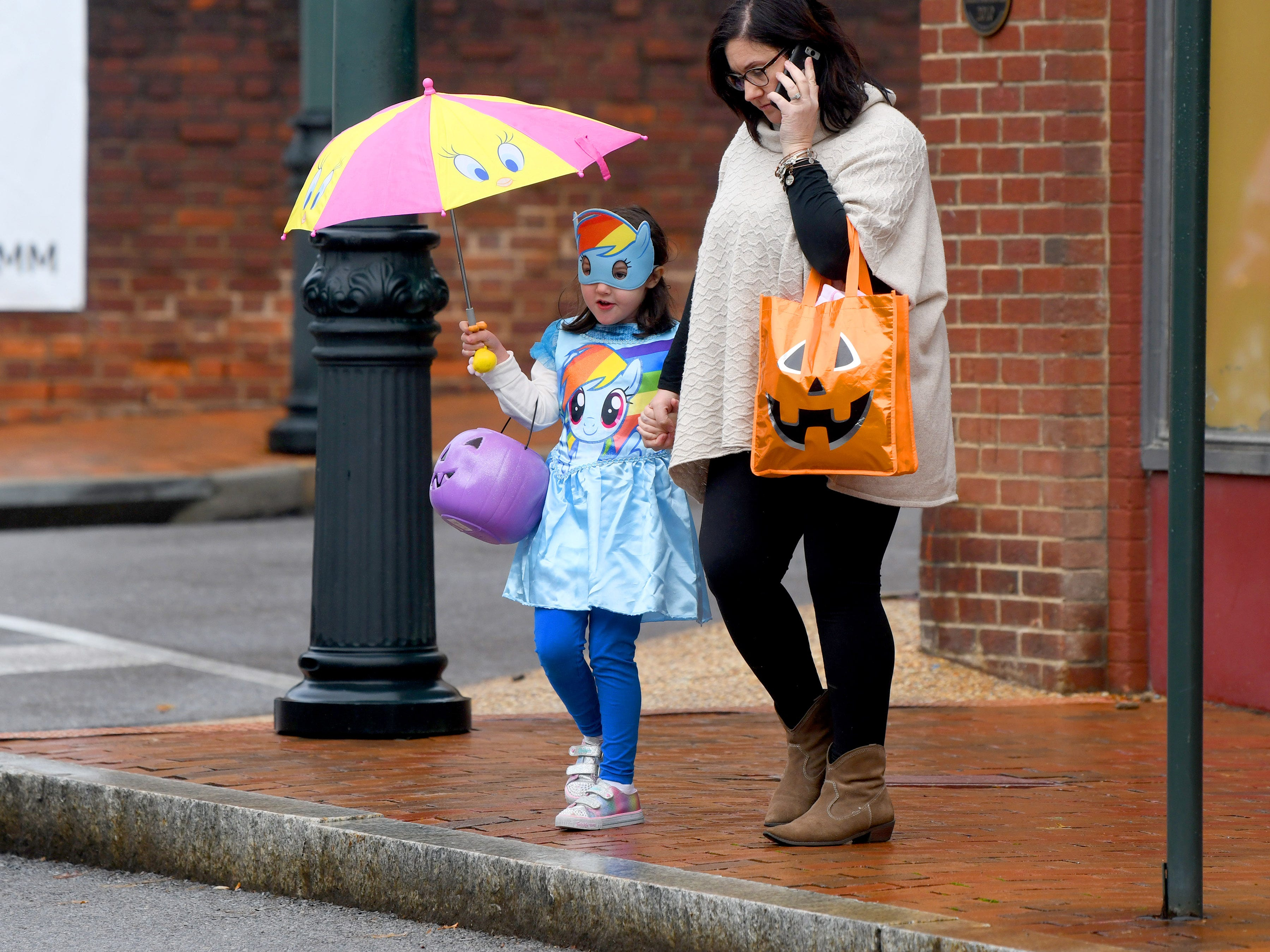 One My Little Pony uses a Tweety Bird umbrella to stay dry while trick-or-treating in downtown Staunton on Saturday, Oct. 27, 2018.