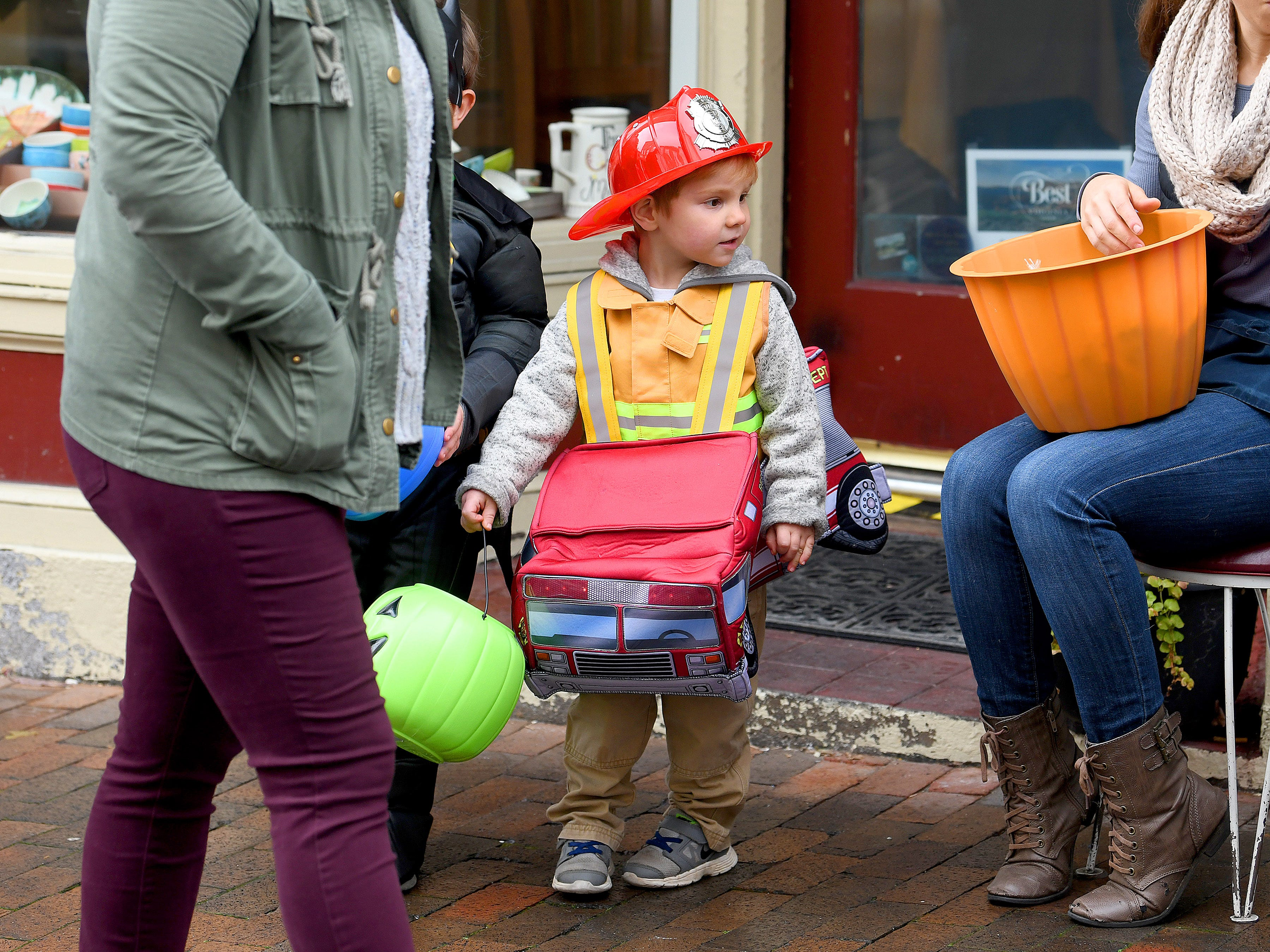 A firefighter trick-or-treats in downtown Staunton on Saturday, Oct. 27, 2018.