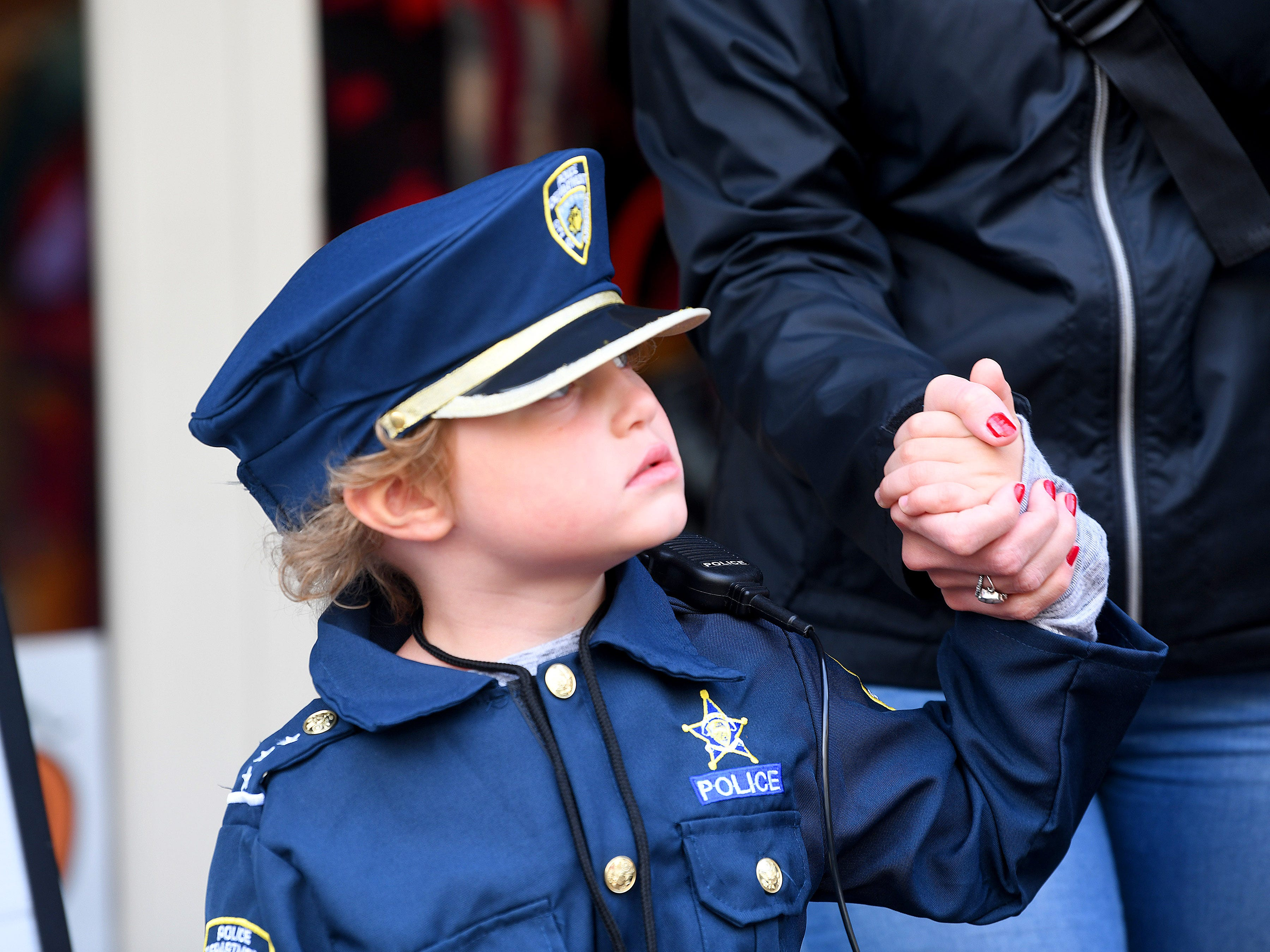 A young police officer  trick-or-treats in downtown Staunton on Saturday, Oct. 27, 2018.