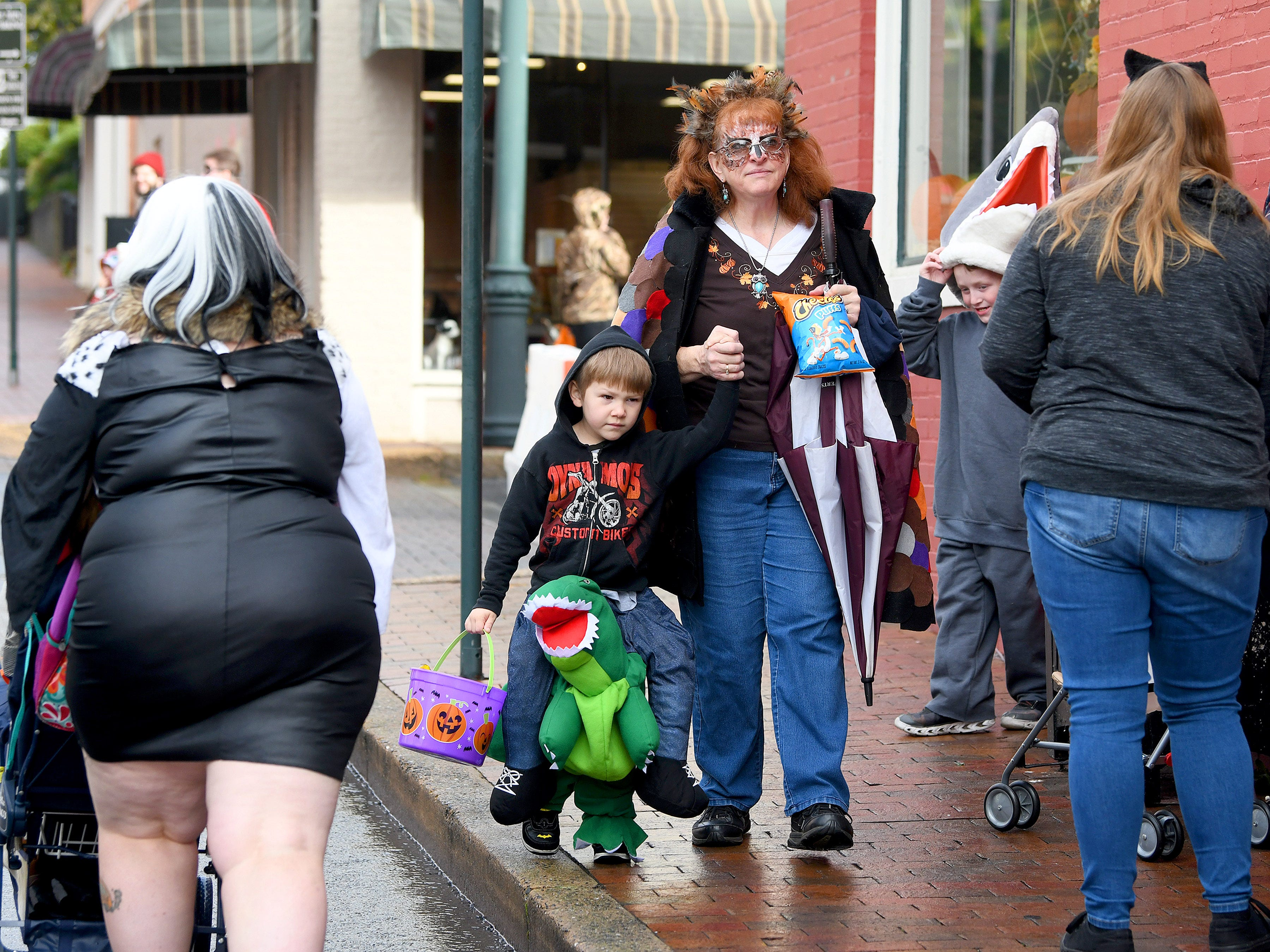 One young trick-or-treater rides a dinosaur during the annual downtown trick-or-treating event in Staunton on Saturday, Oct. 27, 2018.