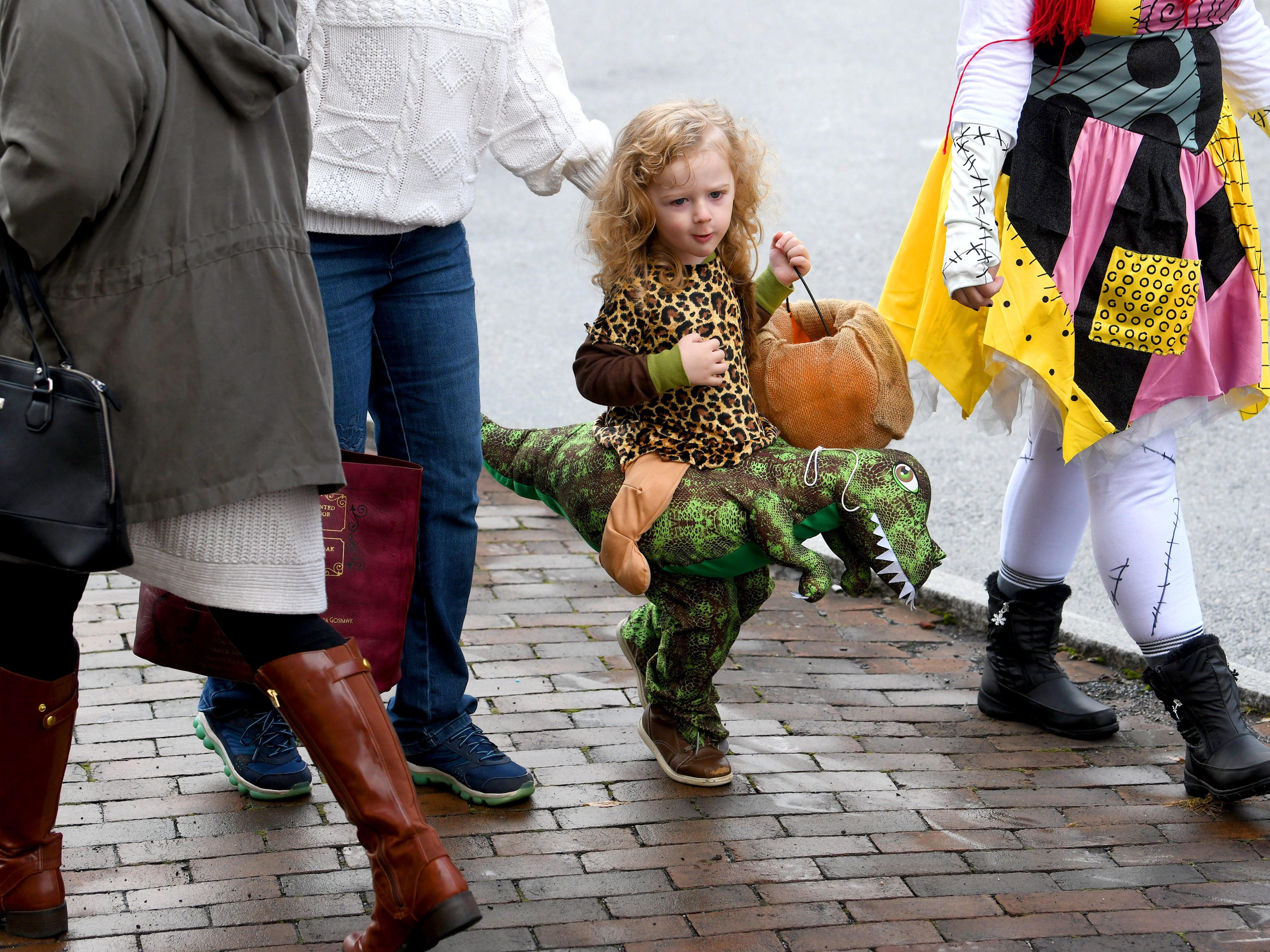 A young trick-or-treater rides a dinosaur during the annual downtown trick-or-treating event in Staunton on Saturday, Oct. 27, 2018.