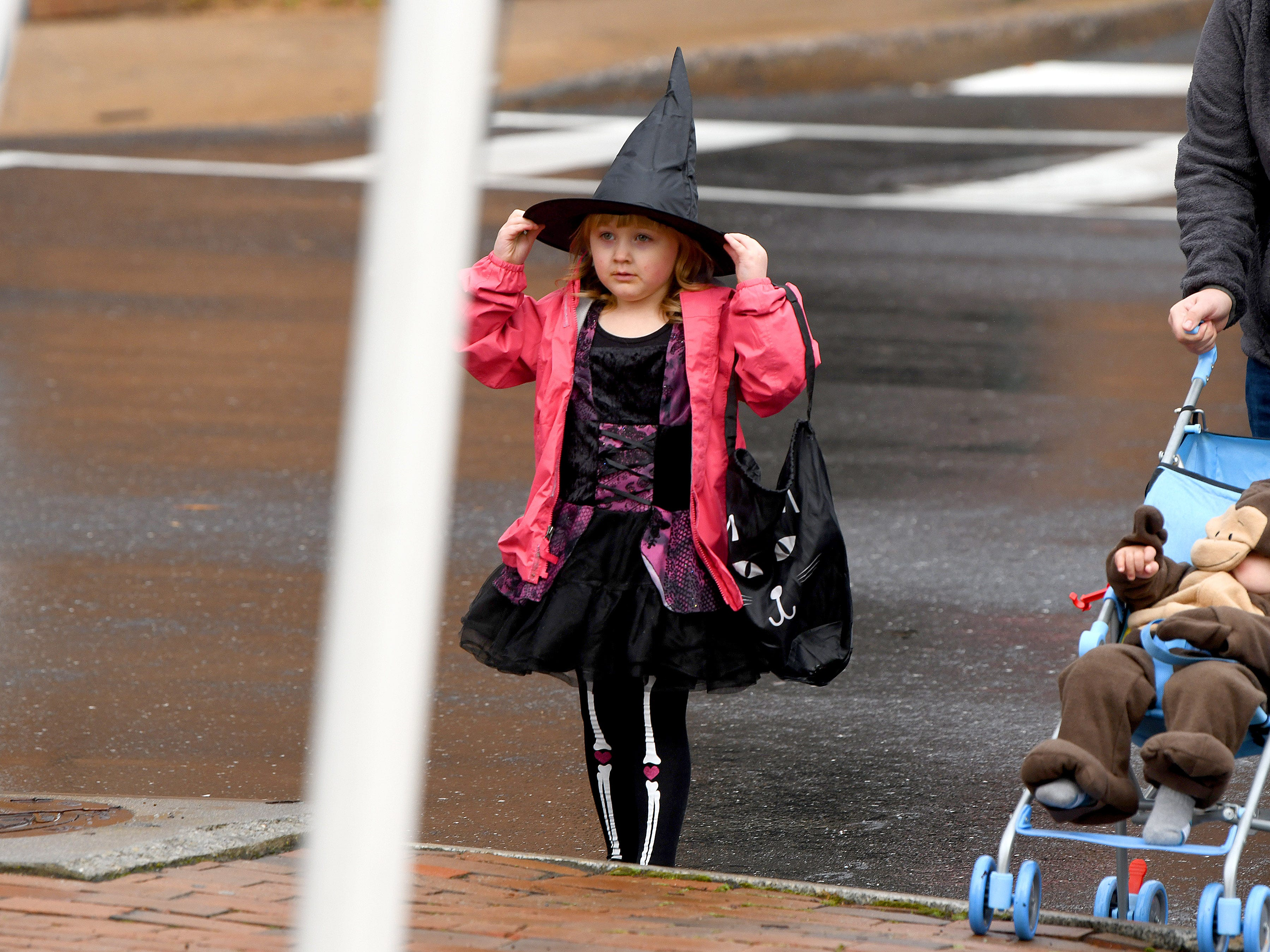 A young witch checks her hat as trick-or-treating begins in downtown Staunton on Saturday, Oct. 27, 2018.