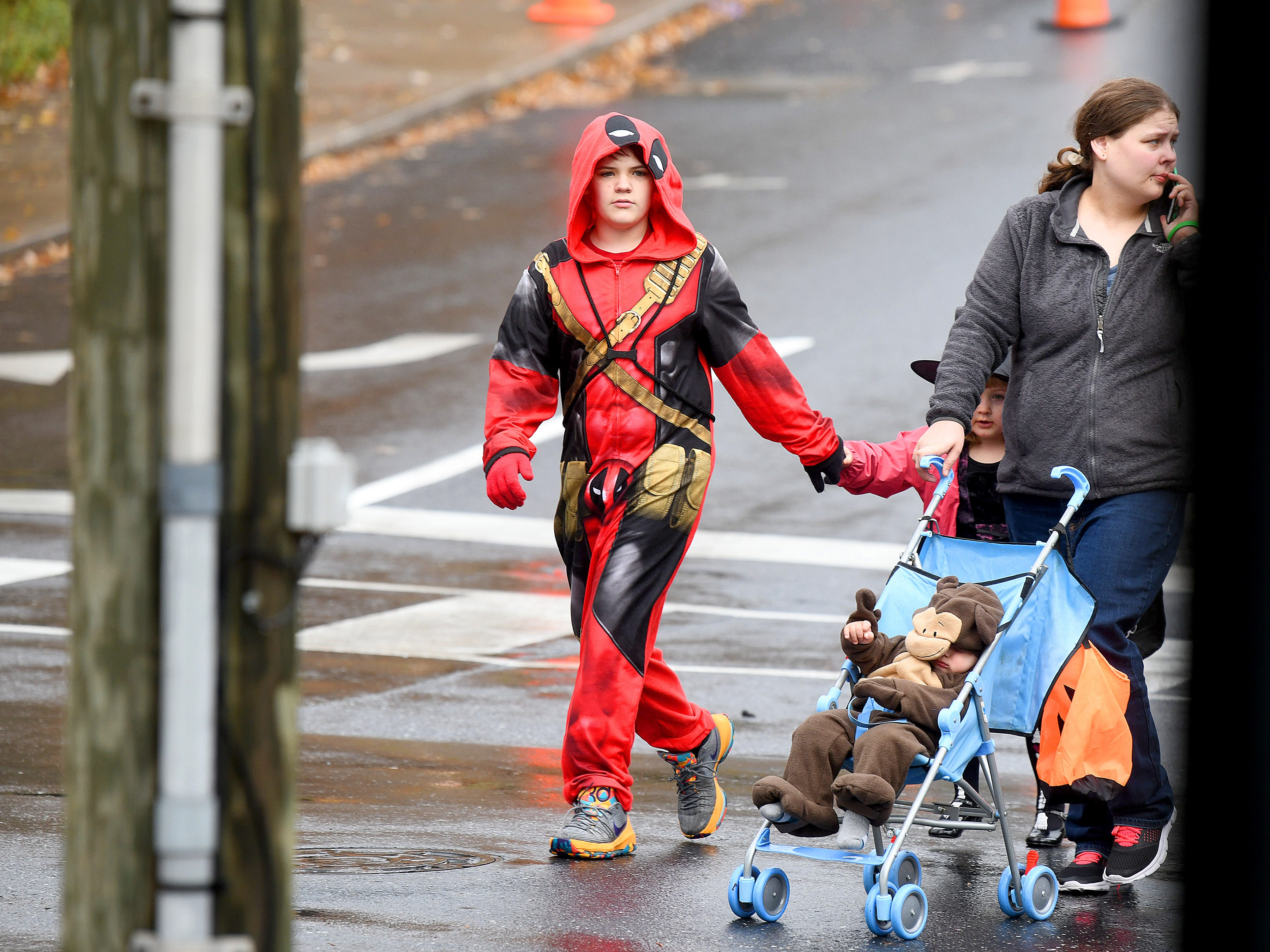 Deadpool helps a young witch cross the street next to a monkey in a stroller while trick-or-treating in downtown Staunton on Saturday, Oct. 27, 2018.
