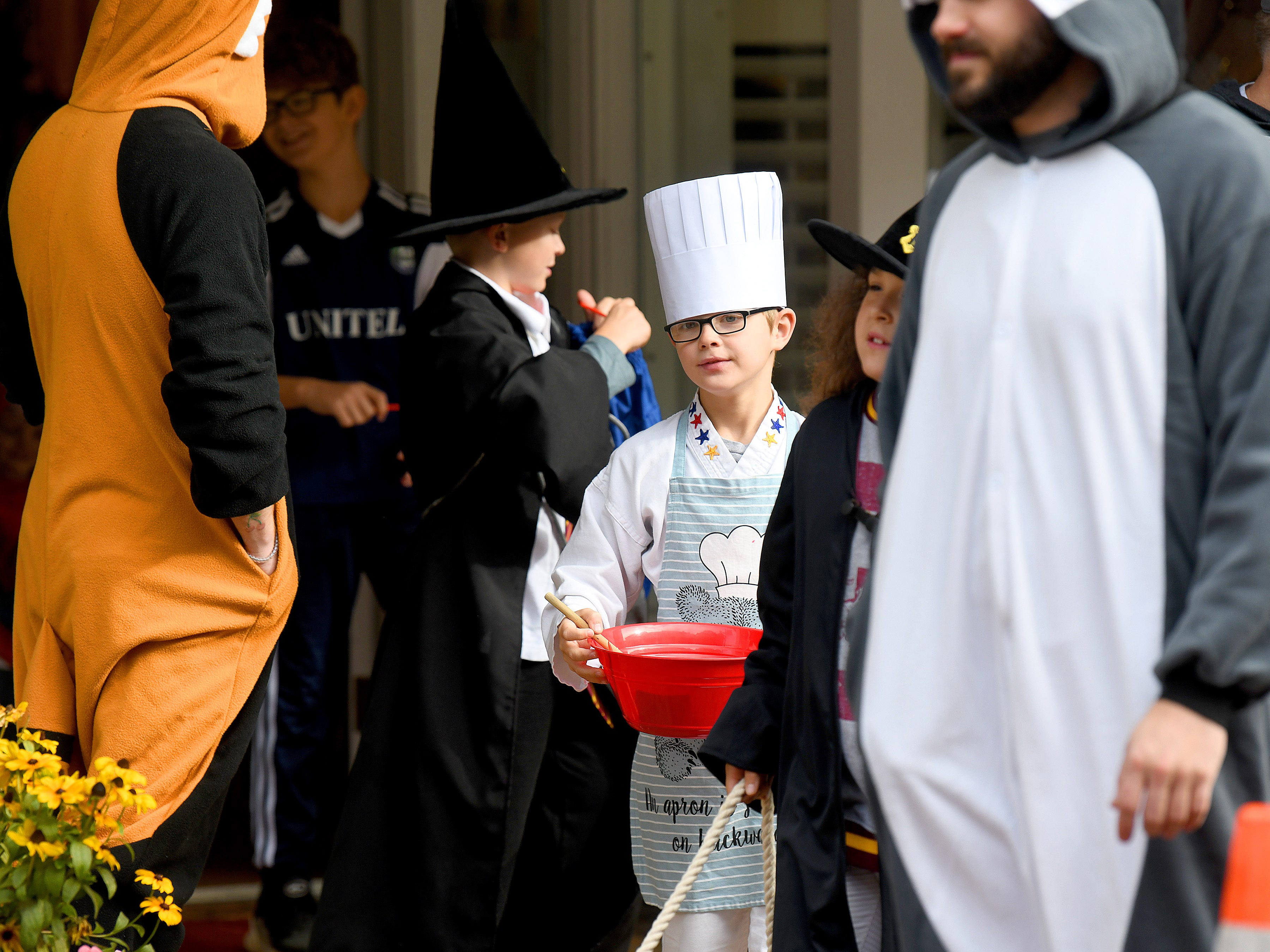 A chef stirs the contents of a mixing bowl while trick-or-treating in downtown Staunton on Saturday, Oct. 27, 2018.
