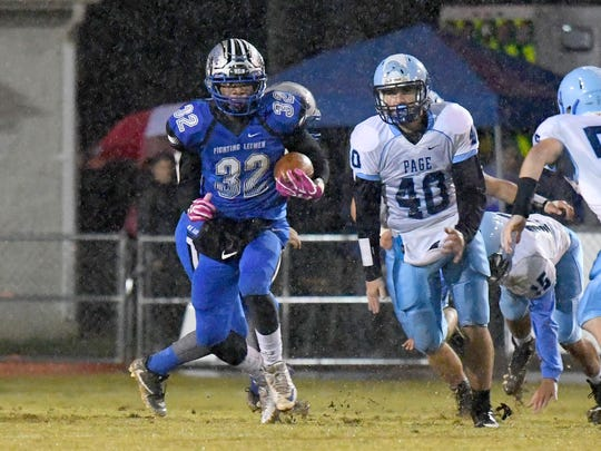 Robert E. Lee's Tajunique Dobbins runs the ball as Page County's David Rothgeb gives chase during a game played in Staunton on Friday, Oct. 26. 2018.