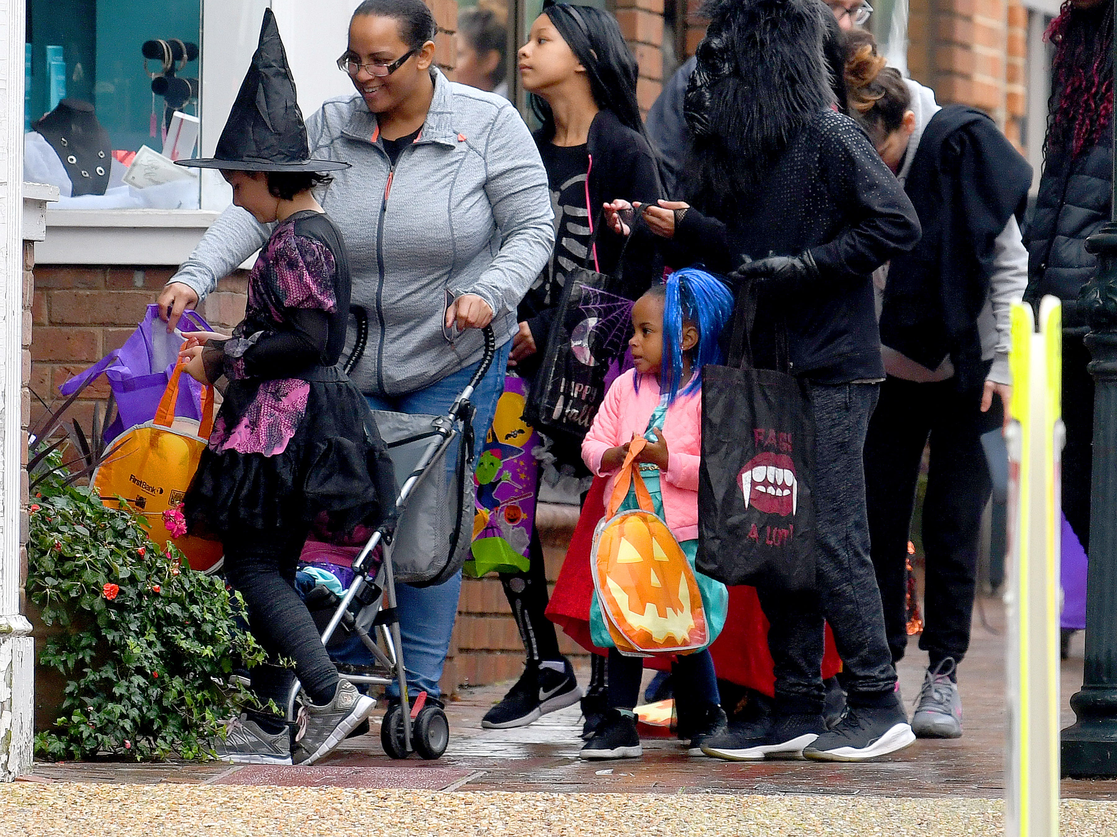 Trick-or-treaters fille a sidewalk while trick-or-treating in downtown Staunton on Saturday, Oct. 27, 2018.