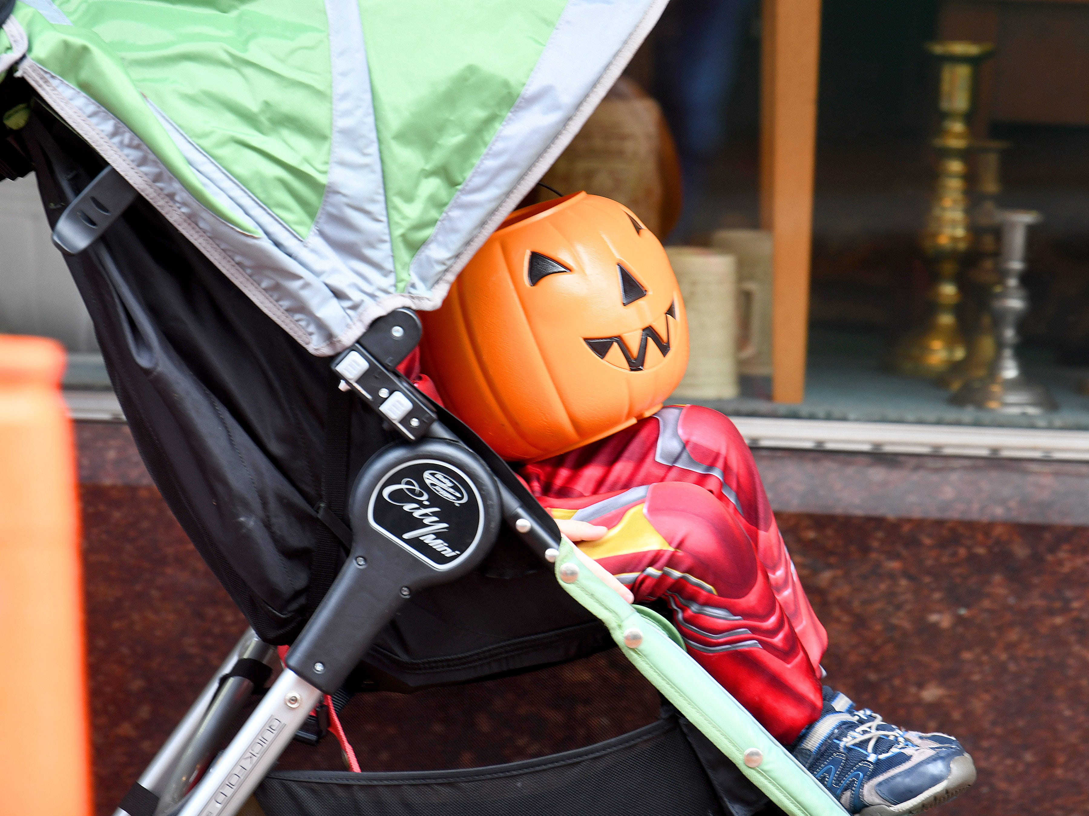 A candy bucket that looks like a Jack-o-Lantern appears to be a smiling face in a stroller during the annual the annual downtown trick-or-treating event in Staunton on Saturday, Oct. 27, 2018.