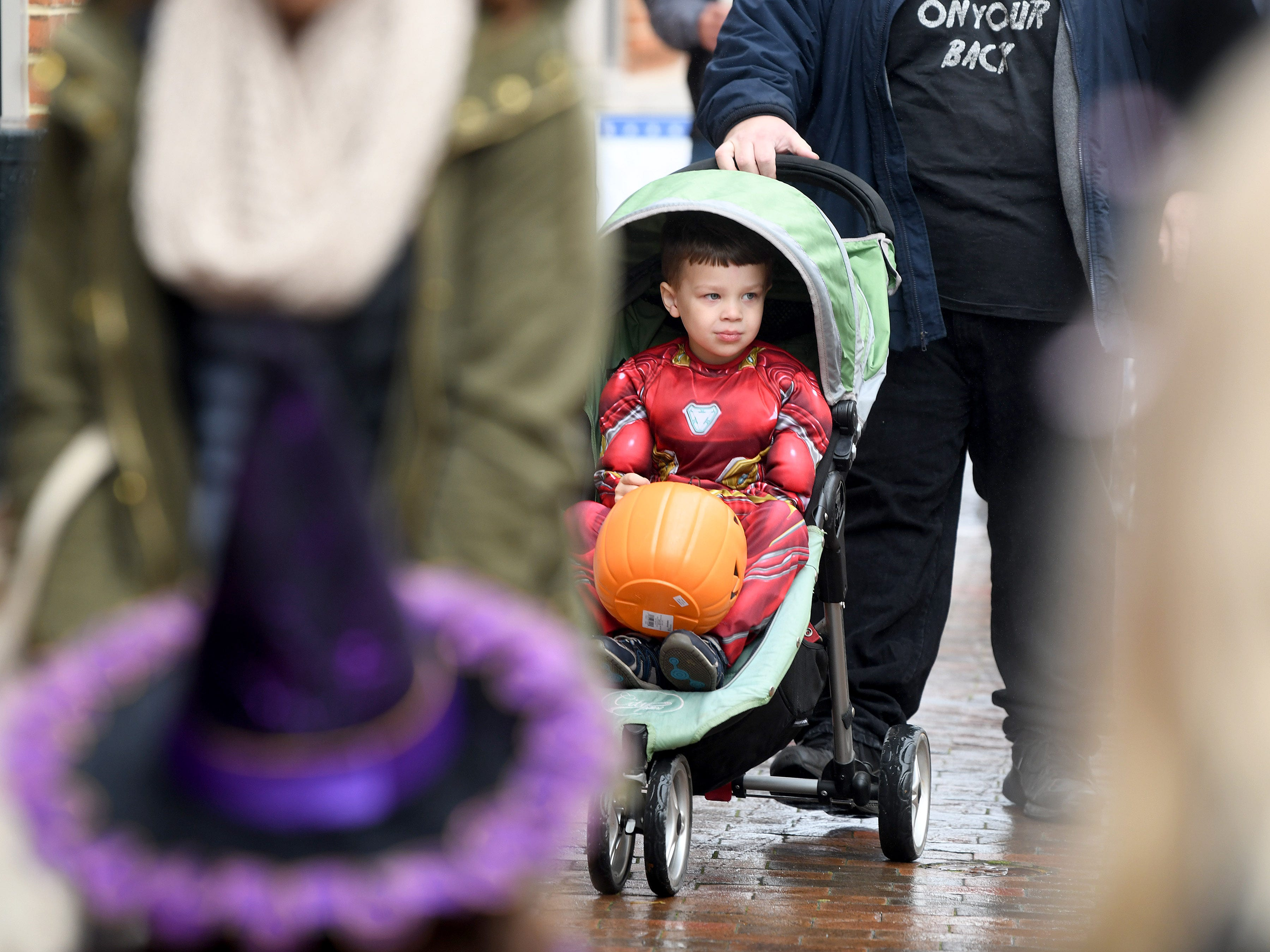 Iron Man holds onto his bucket of candy while riding in a stroller for trick-or-treating in downtown Staunton on Saturday, Oct. 27, 2018.