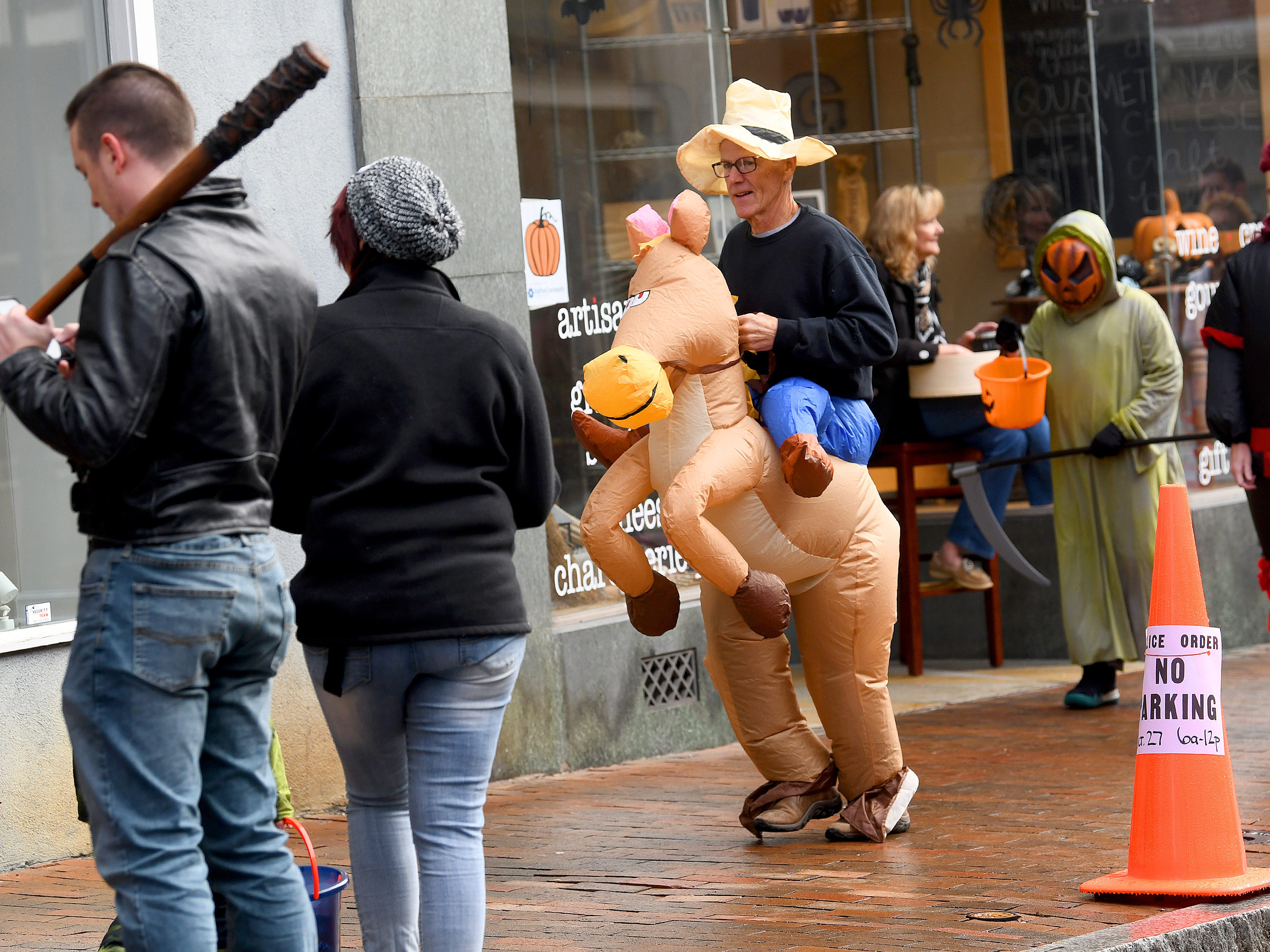 A man gallops along the sidewalk with his inflatable horse during the annual downtown trick-or-treating event in Staunton on Saturday, Oct. 27, 2018.