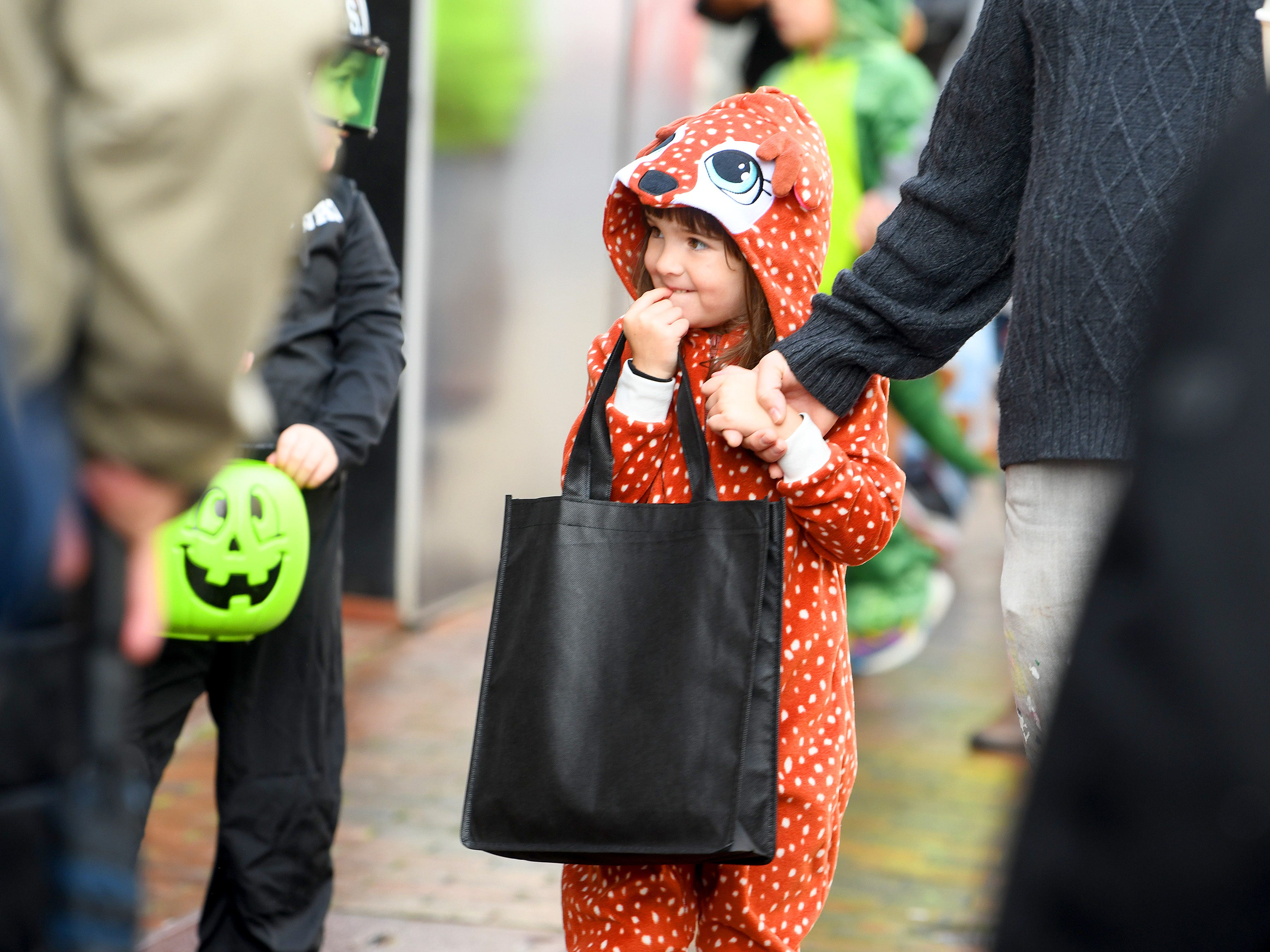 A young trick-or-treater smiles while holding onto her bag while trick-or-treating in downtown Staunton on Saturday, Oct. 27, 2018.