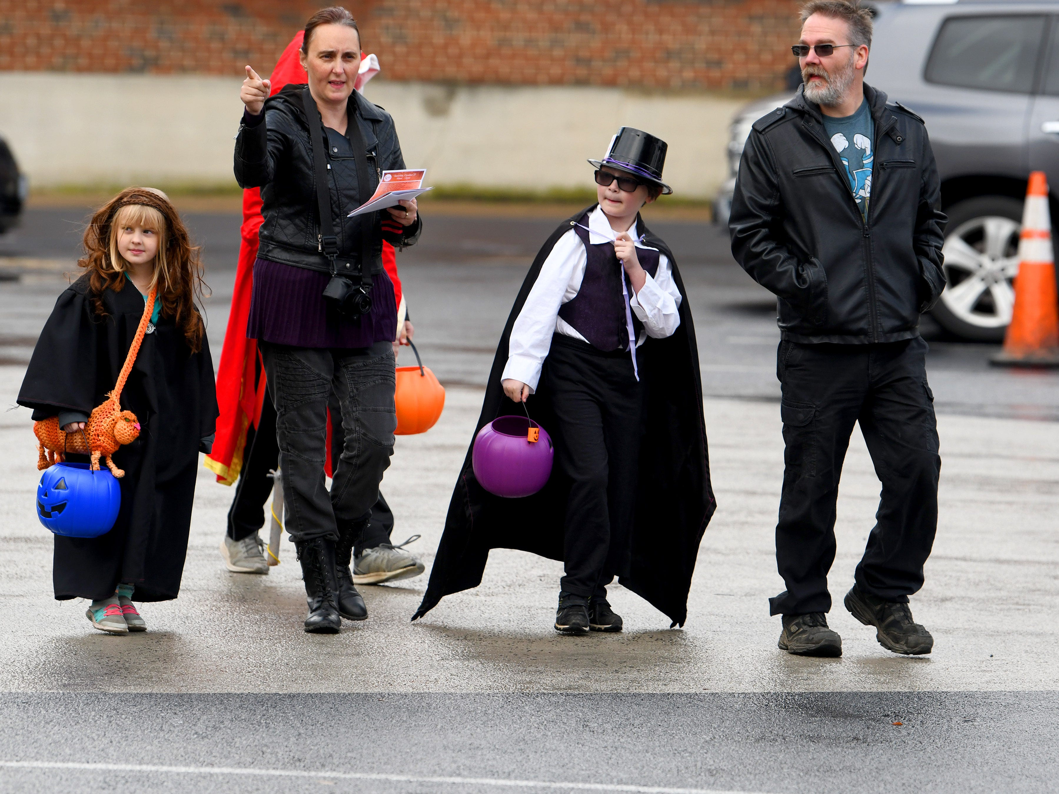 Trick-or-treaters cross a parking lot during the annual downtown trick-or-treating event in Staunton on Saturday, Oct. 27, 2018.