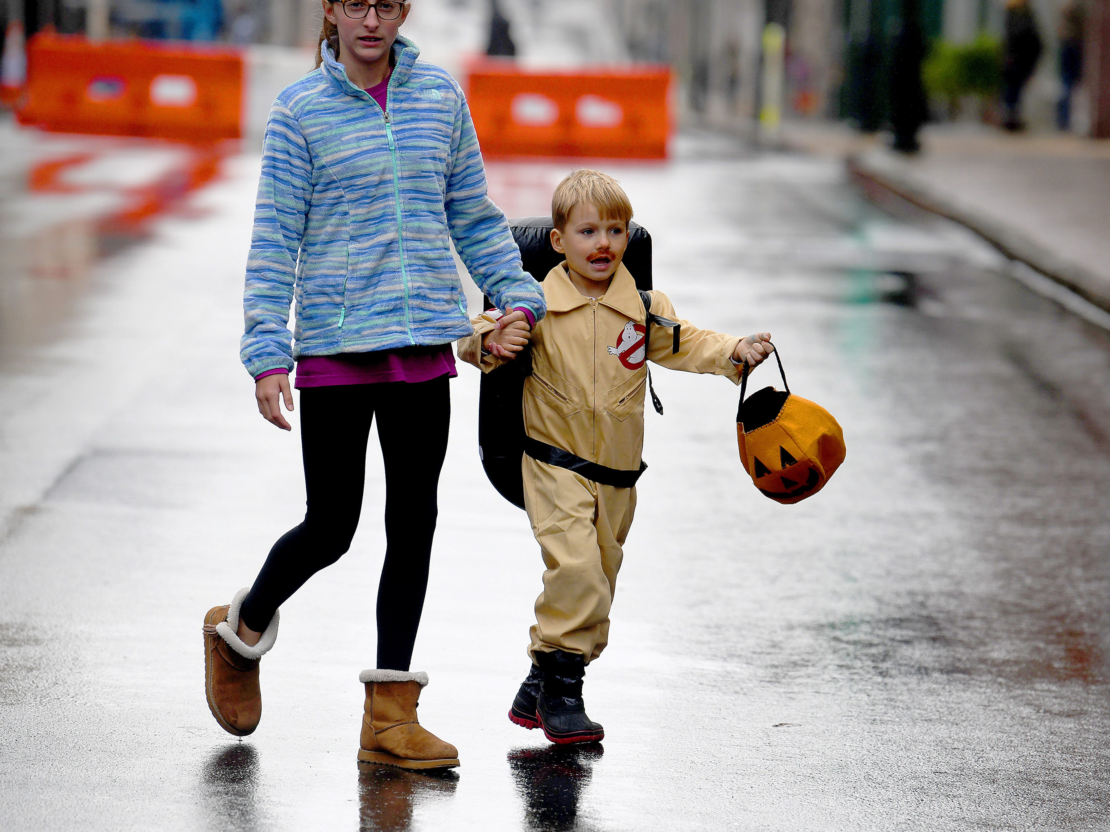 A Ghosterbuster crosses a closed off street in search of candy while trick-or-treating in downtown Staunton on Saturday, Oct. 27, 2018.