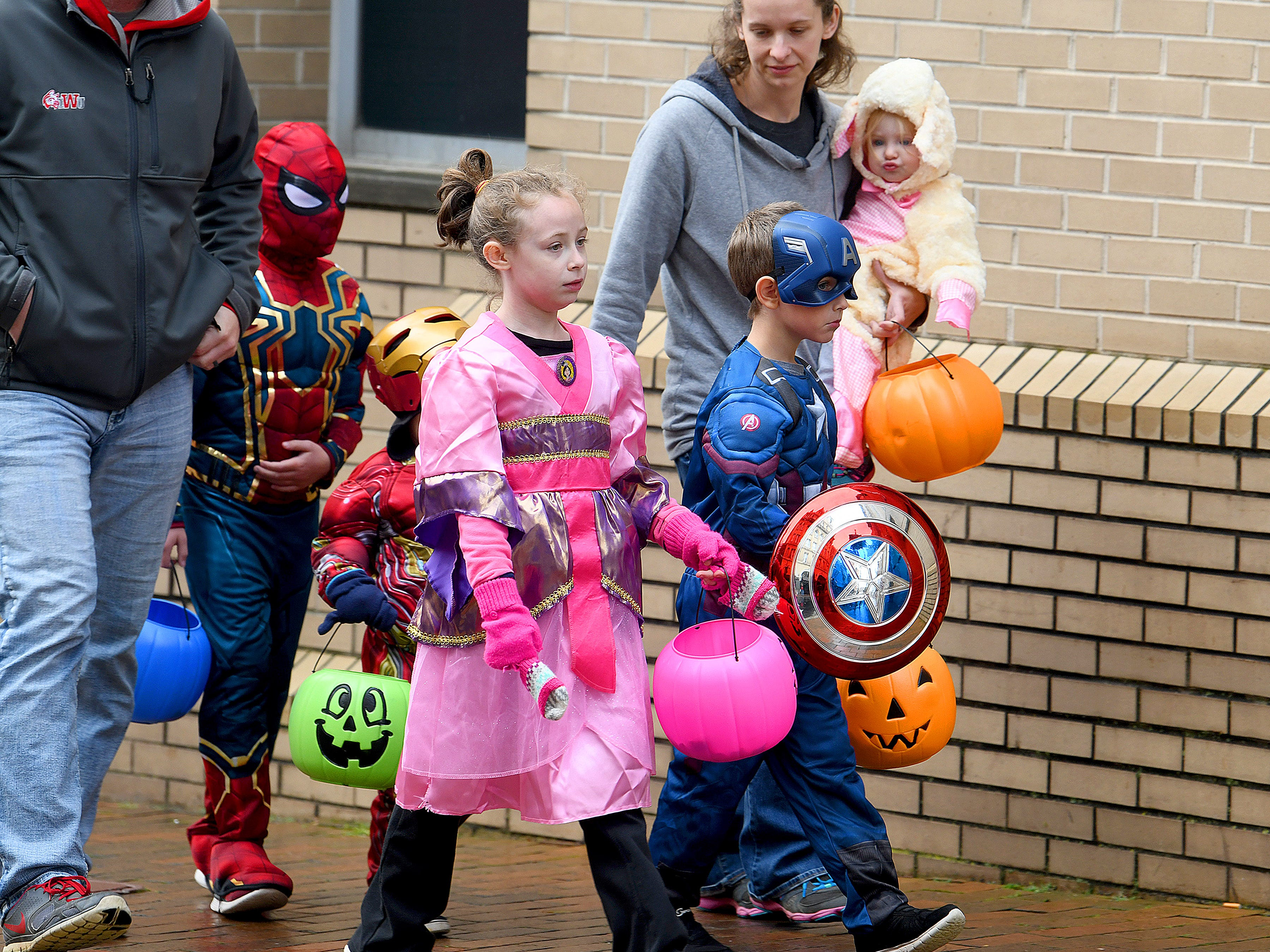 Superheroes blend in with other trick-or-treaters while making the rounds during the annual downtown trick-or-treating event in Staunton on Saturday, Oct. 27, 2018.