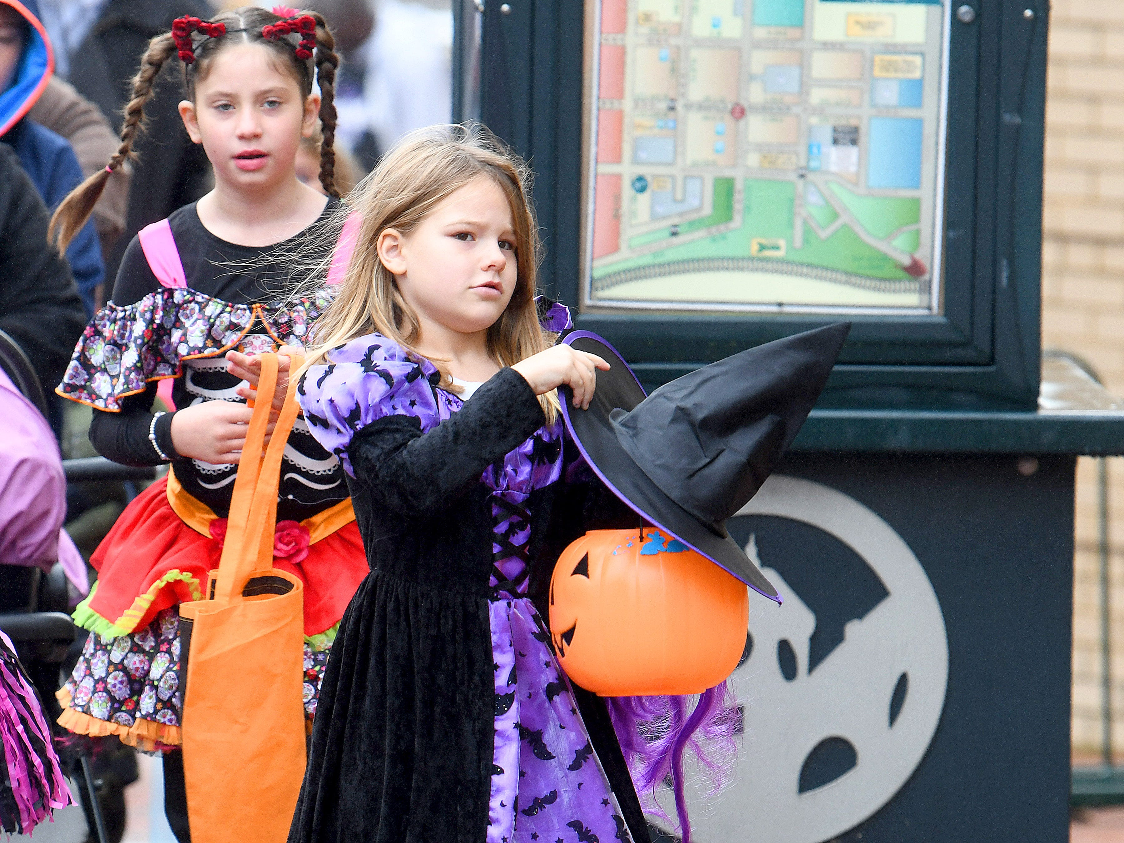 A young witch works with her hat  while trick-or-treating in downtown Staunton on Saturday, Oct. 27, 2018.