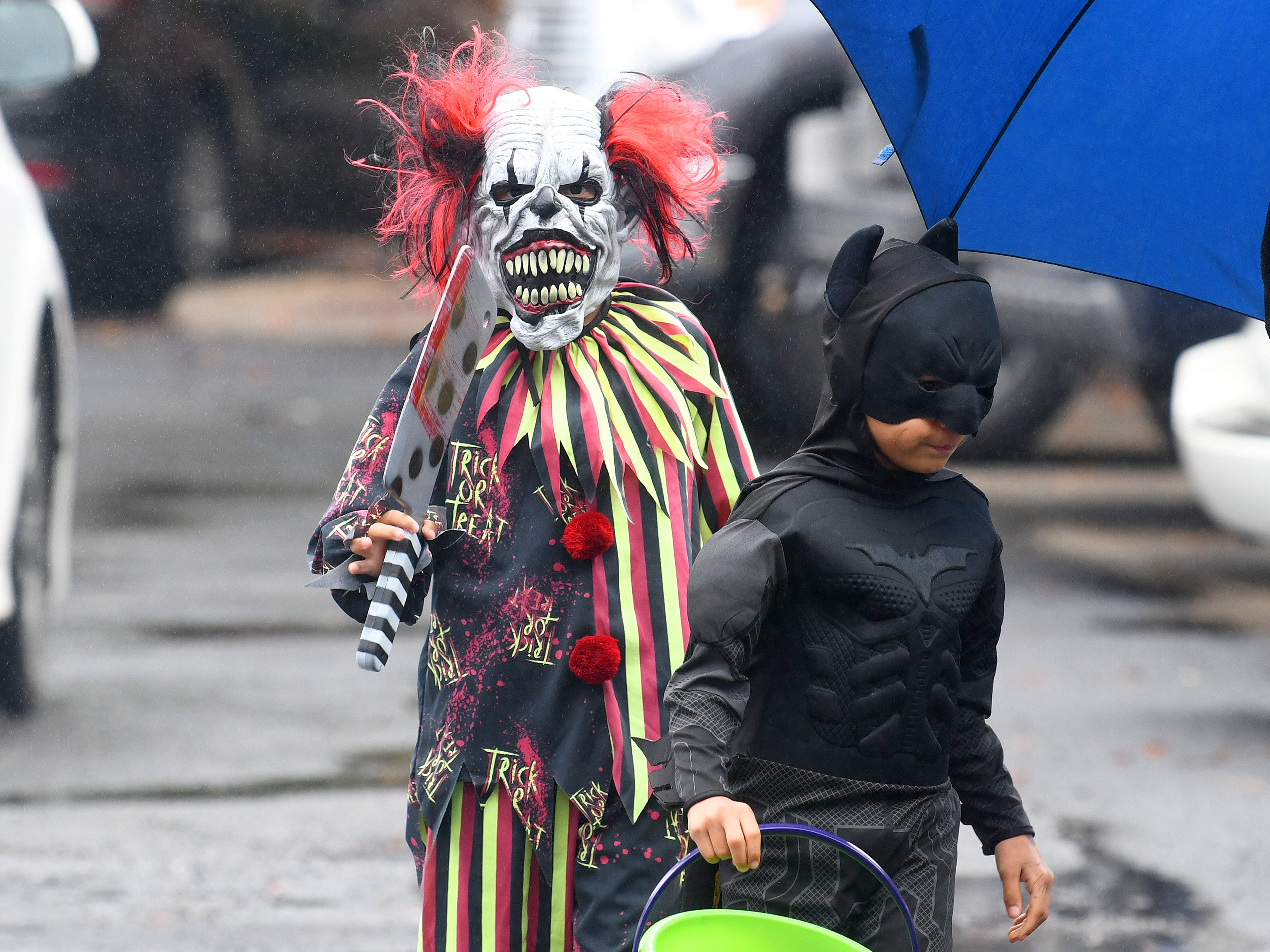 A clown that seems fitting to the season seems to be following Batman while trick-or-treating in downtown Staunton on Saturday, Oct. 27, 2018.