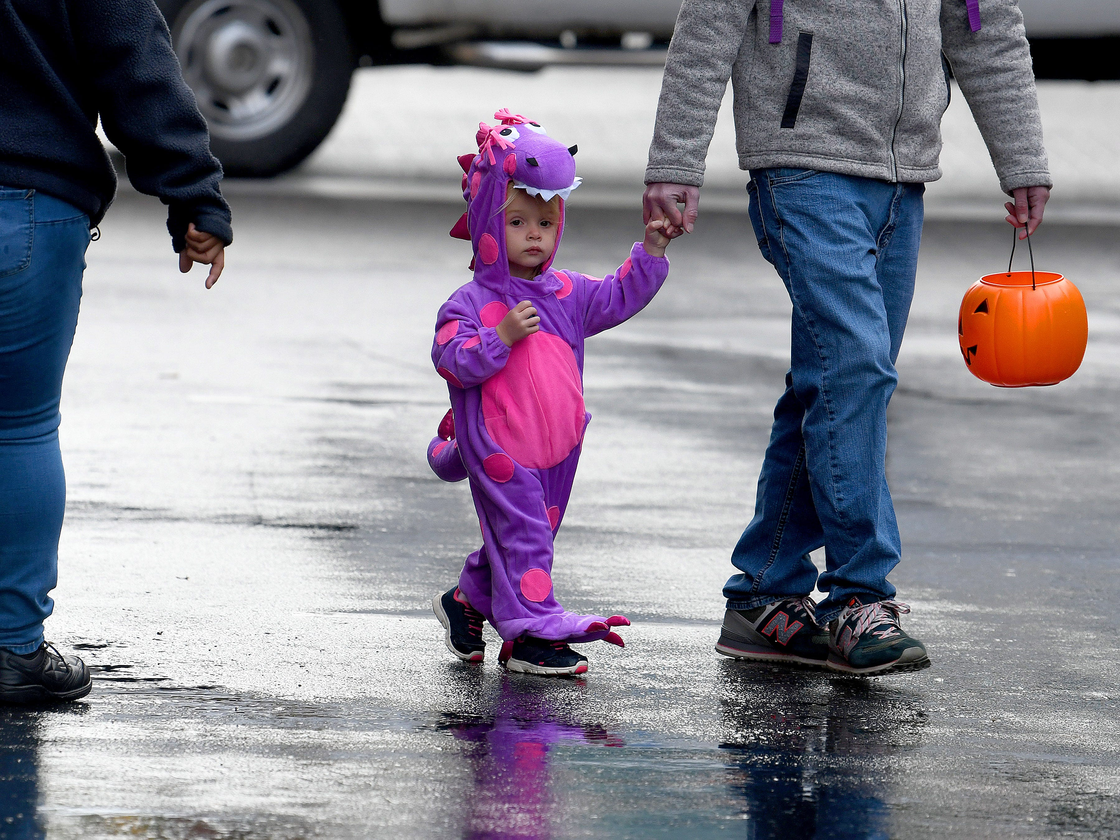 A young trick-or-treater holds an adult hand while crossing a closed street in search of more treats on the opposite side while trick-or-treating in downtown Staunton on Saturday, Oct. 27, 2018.