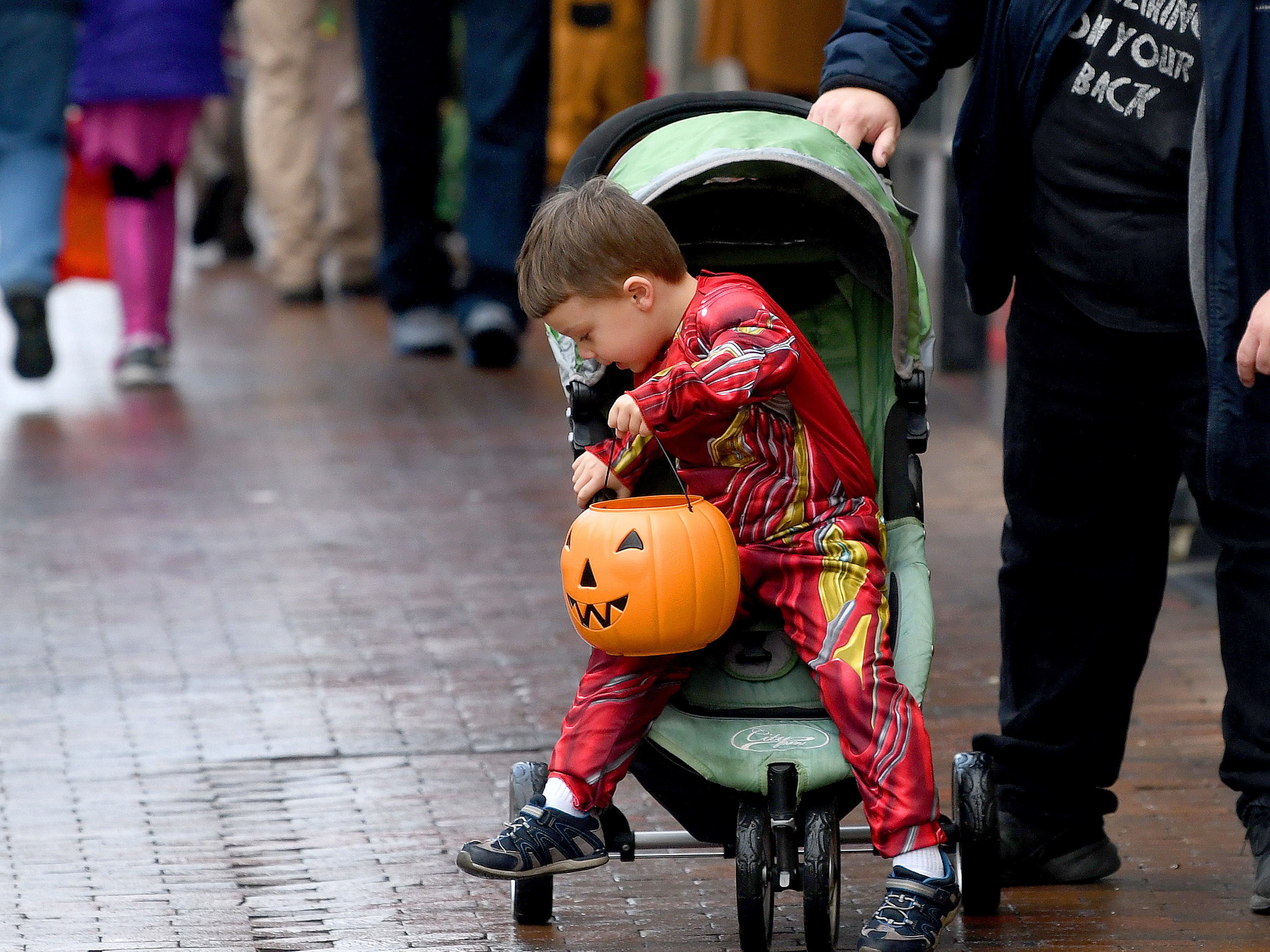 Iron Man hops out of his stroller on a quest for more treats while trick-or-treating in downtown Staunton on Saturday, Oct. 27, 2018.