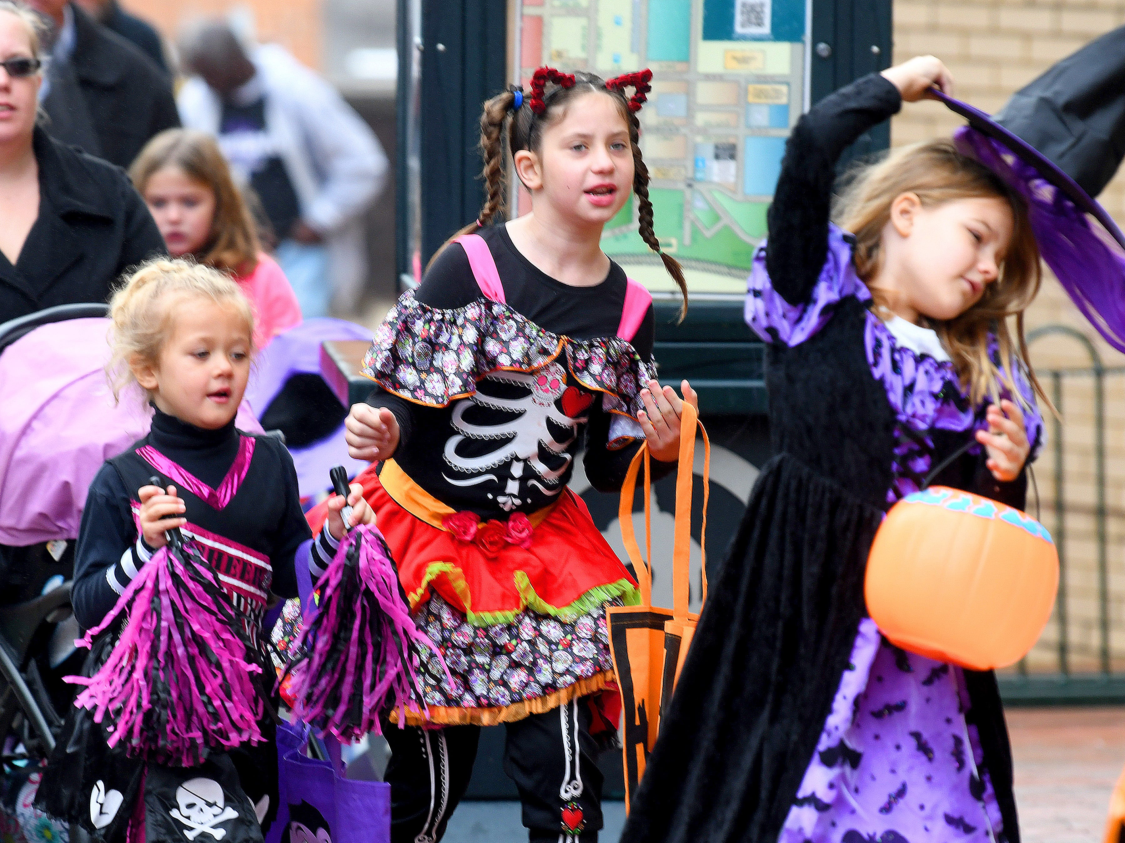 "A cheerleader walks alongside a character from the movie ""CoCo"" as they both follow a witch during the annual downtown trick-or-treating event in Staunton on Saturday, Oct. 27, 2018."