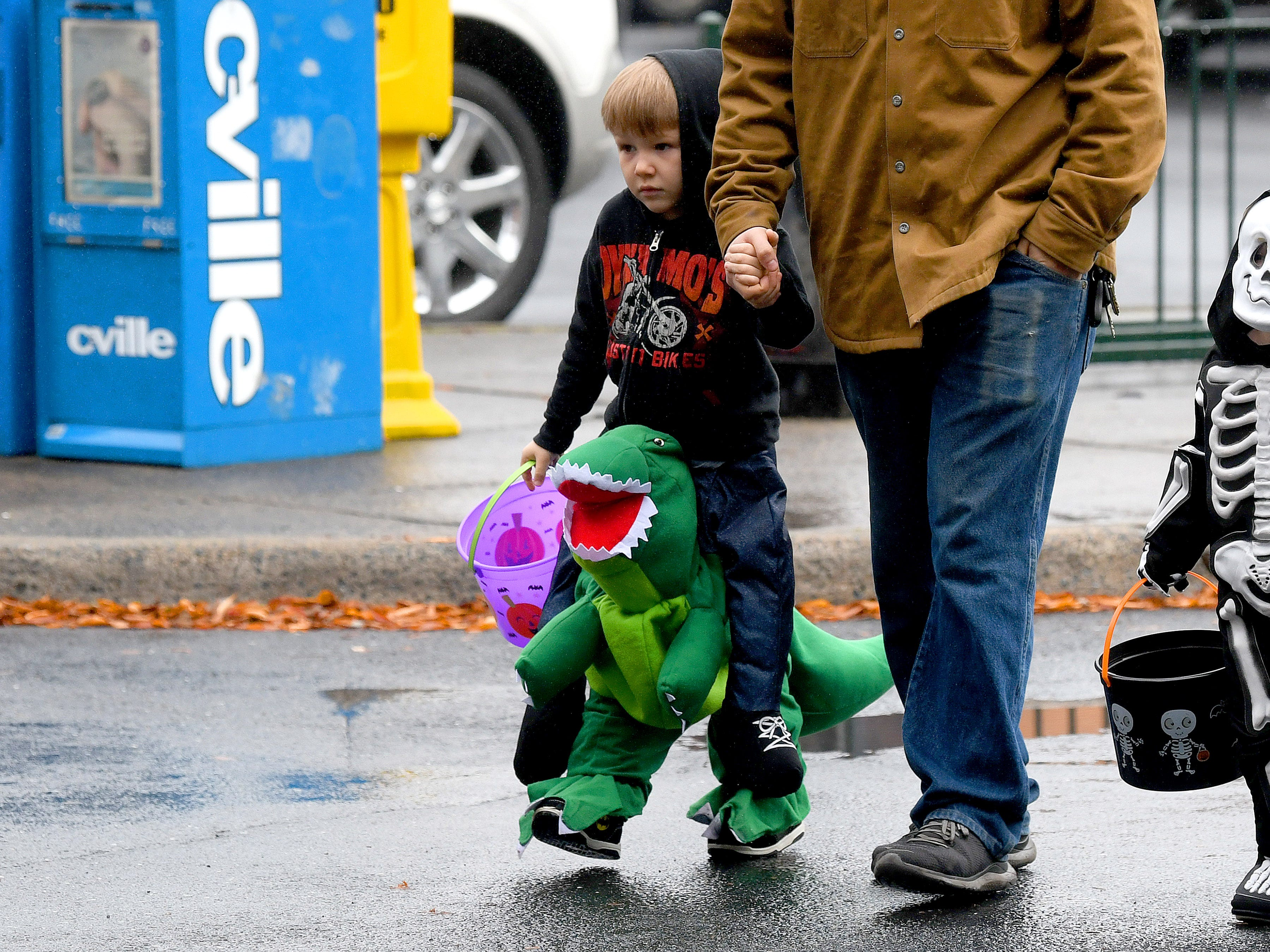 One trick-or-treater rides a dinosaur while trick-or-treating in downtown Staunton on Saturday, Oct. 27, 2018.