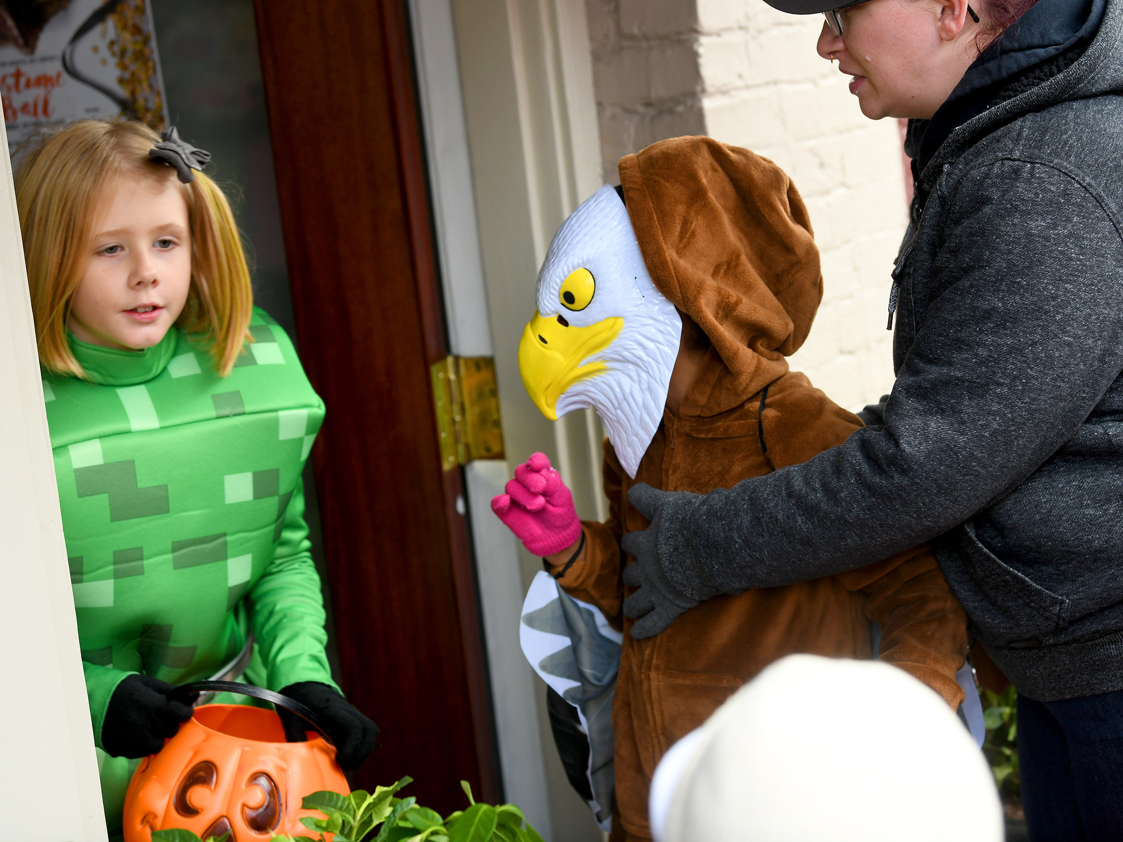 An eagle heads into a shop for candy as a Minecraft character comes out while trick-or-treating in downtown Staunton on Saturday, Oct. 27, 2018.