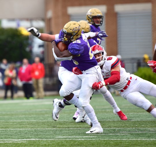 James Madison's Cardon Johnson struggles for extra yardage during the first half of the Dukes' Colonial Athletic Association football game against Stony Brook at Bridgeforth Stadium in Harrisonburg, Va., on Saturday, Oct. 27, 2018.