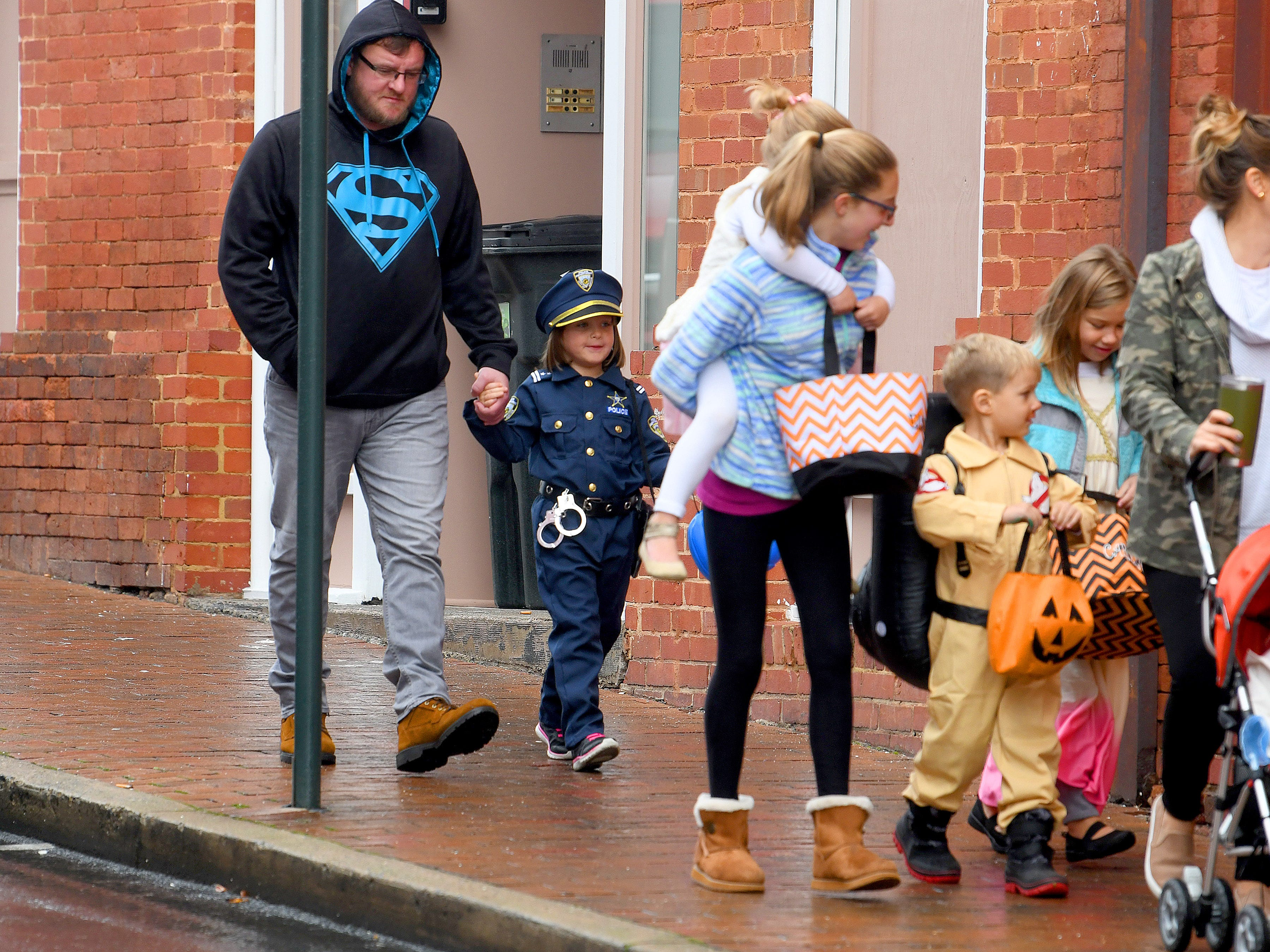 A young police officer holds an adult hand while trick-or-treating in downtown Staunton on Saturday, Oct. 27, 2018.