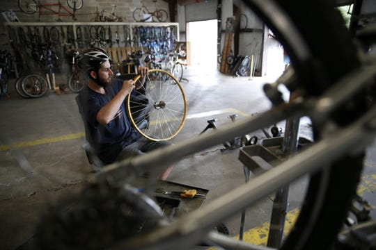 Volunteer Justin Rice works on adjusting a bike wheel's rim strip at the Bicycle House in 2015.