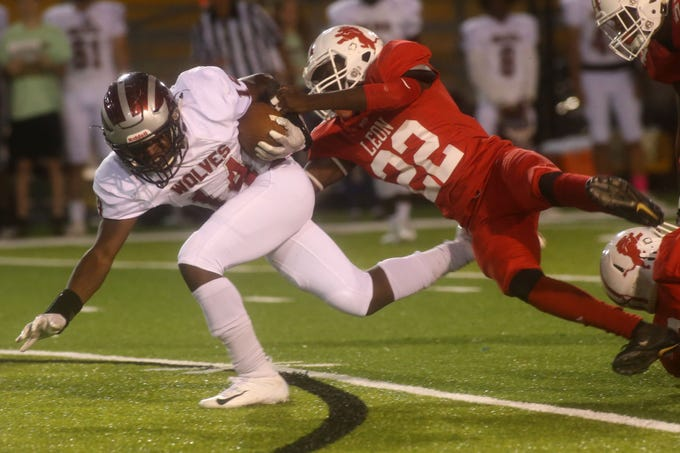 Chiles running back Chase Gillespie (14) is tackled by Leon/s Marvin Easley (22) during a game Friday at Gene Cox Stadium. Gillespie ran for 111 yards and two touchdowns as Chiles won 48-13.