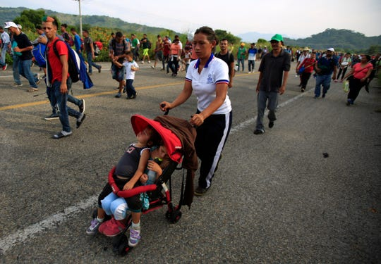 A woman pushes two children in a single stroller as migrants advance after Mexican police briefly blockaded the road, outside the town of Arriaga, Mexico, on Saturday, Oct. 27, 2018. Hundreds of Mexican federal officers carrying plastic shields blocked the caravan of Central American migrants from continuing toward the United States, after several thousand of the migrants turned down the chance to apply for refugee status and obtain a Mexican offer of benefits.
