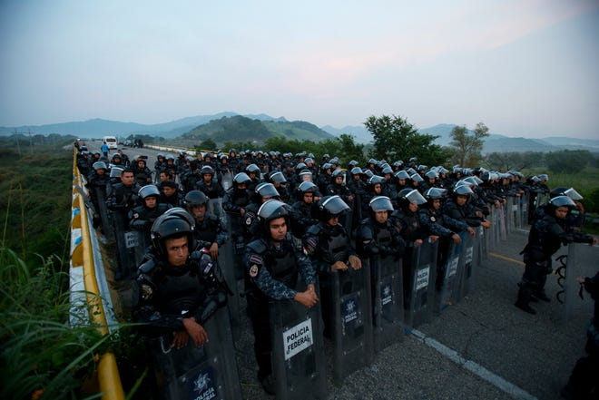 Police in riot gear block the highway to stop a caravan of thousands of Central American migrants from advancing, outside Arriaga, Chiapas state, Mexico, on Saturday, Oct. 27, 2018. Migrants declined to accept a deal offered by the Mexican government allowing them to apply for refugee status if they halted their journey in the southern states of Chiapas and Oaxaca. Eventually, police let them pass, with the agreement that the dialogue with authorities would continue at their next stop.