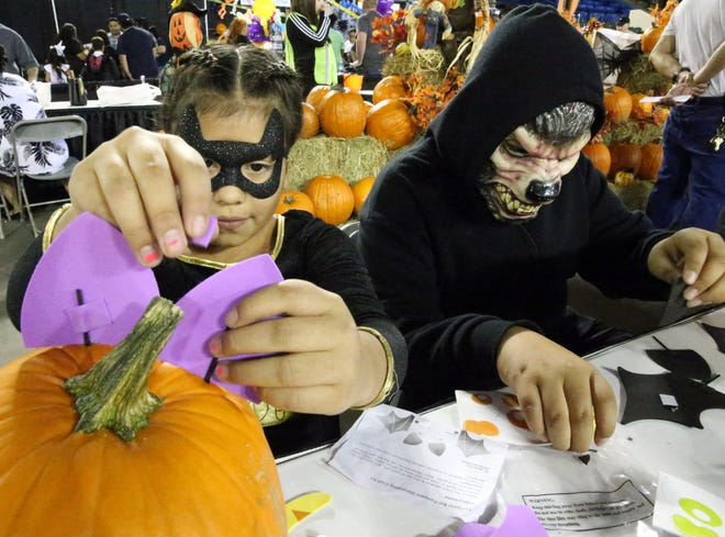 Amy Bueno, 9, and her brother, Moses Muñoz, 11, attach stickers to real pumpkins in a pumpkin patch at the 28th Junior Woman's Club of El Paso Spooktacular at the El Paso County Coliseum.