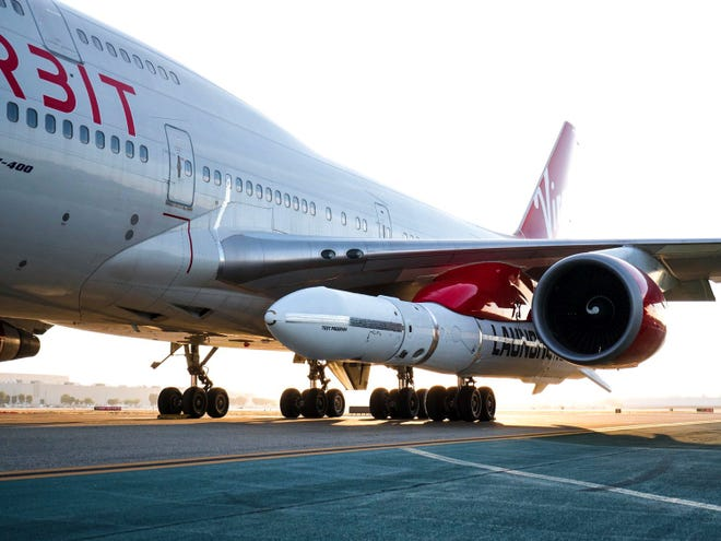 """In this Thursday photo released by Virgin Orbit, a completed LauncherOne rocket hangs from the wing of Cosmic Girl, a Boeing 747 aircraft used as the rocket's """"flying launch pad,"""" at the Long Beach Airport."""
