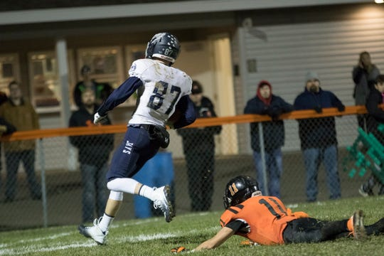 Menasha receiver Jordan Nichols heads into the end zone in front of a diving attempt by Marshfield's Joey Goettl to score on a 52-yard catch and run during the fourth quarter Friday.