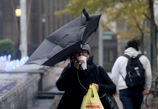 Denise Saintsil of White Plains contends with her coffee and a failed umbrella as she walks through wind blown rain on Main St. in White Plains Oct. 27, 2017.