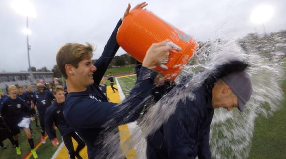 Briarcliff's Will Zimmerman dumps a water bucket on head coach Brandon Beck after their 3-2 win over Blind Brook in the Class B Section 1 boys soccer championship at Lakeland Oct. 27, 2018.