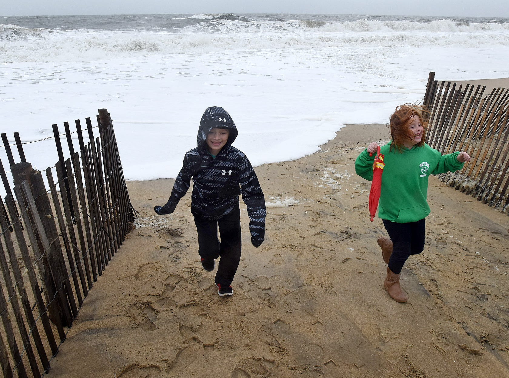 Chase and Aubrey Chmielewski from Towson, MD. run from the ocean as Rehoboth Beach's Annual Sea Witch Festival is underway despite a Nor'easter passing over the beach area. The ocean is coming up to the Dune Line as sea foam spray's the beach as high winds have blown sand on the boardwalk. There was a Kids Bike Parade on the boardwalk Friday afternoon along with a Kids Train Ride in Grove Park.  Special to the News Journal / CHUCK SNYDER