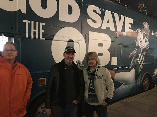 Eagles fans Phillip Mattox, right, and Jeff Daugherty, standing next to the Eagles' double-decker bus outside The Admiralty in London.