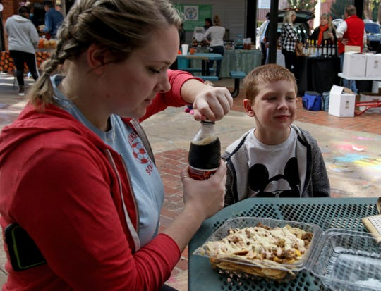 Mindy Hohfeld and her son Elijah get ready to eat western burger nachos Saturday, Oct. 27, 2018, at the downtown Wichita Falls Farmers Market.