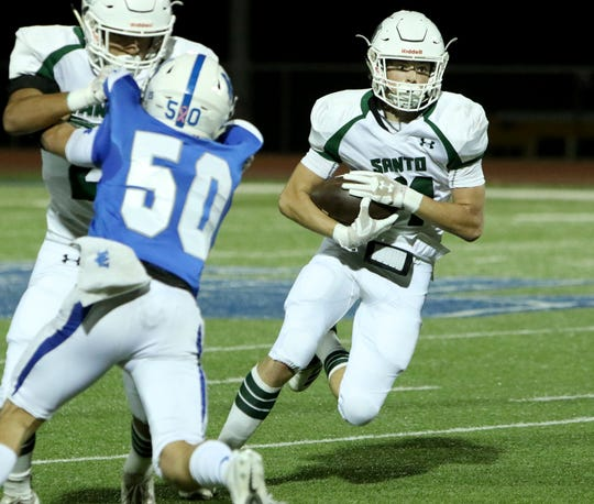 Santo's Grant Nemeth runs through the line of scrimmage against Windthorst Friday, Oct. 26, 2018, in Windthorst. The Trojans defeated the Wildcats 33-26.
