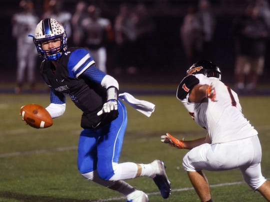 Ben Everson scrambles way from Marietta's Cory Warrener during Zanesville's 41-7 win on Friday night at John D. Sulsberger Memorial Stadium.