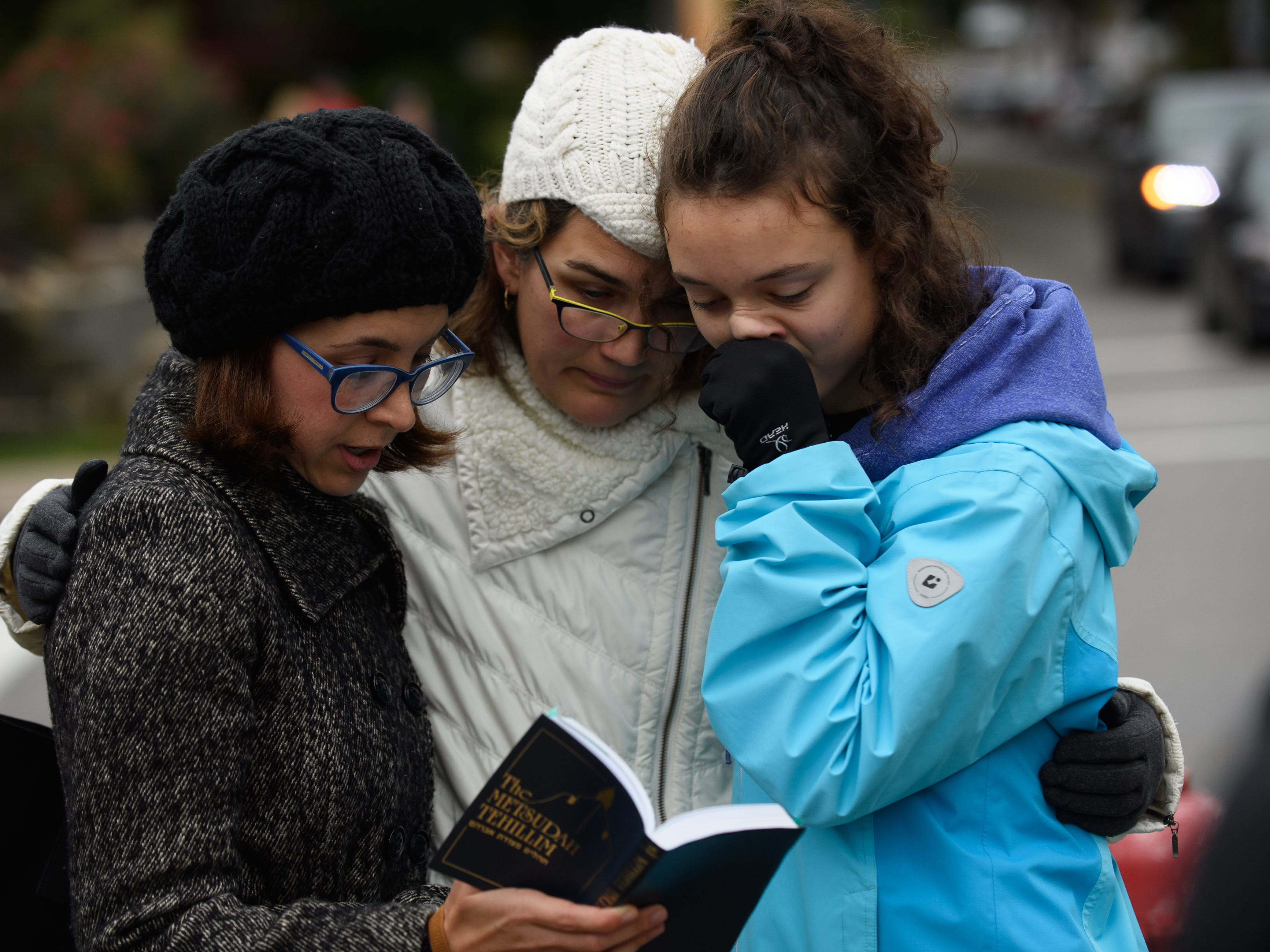 Tammy Hepps, left, Kate Rothstein and her daughter, Simone Rothstein, 16, pray from a prayerbook a block away from the site of a mass shooting at the Tree of Life Synagogue.